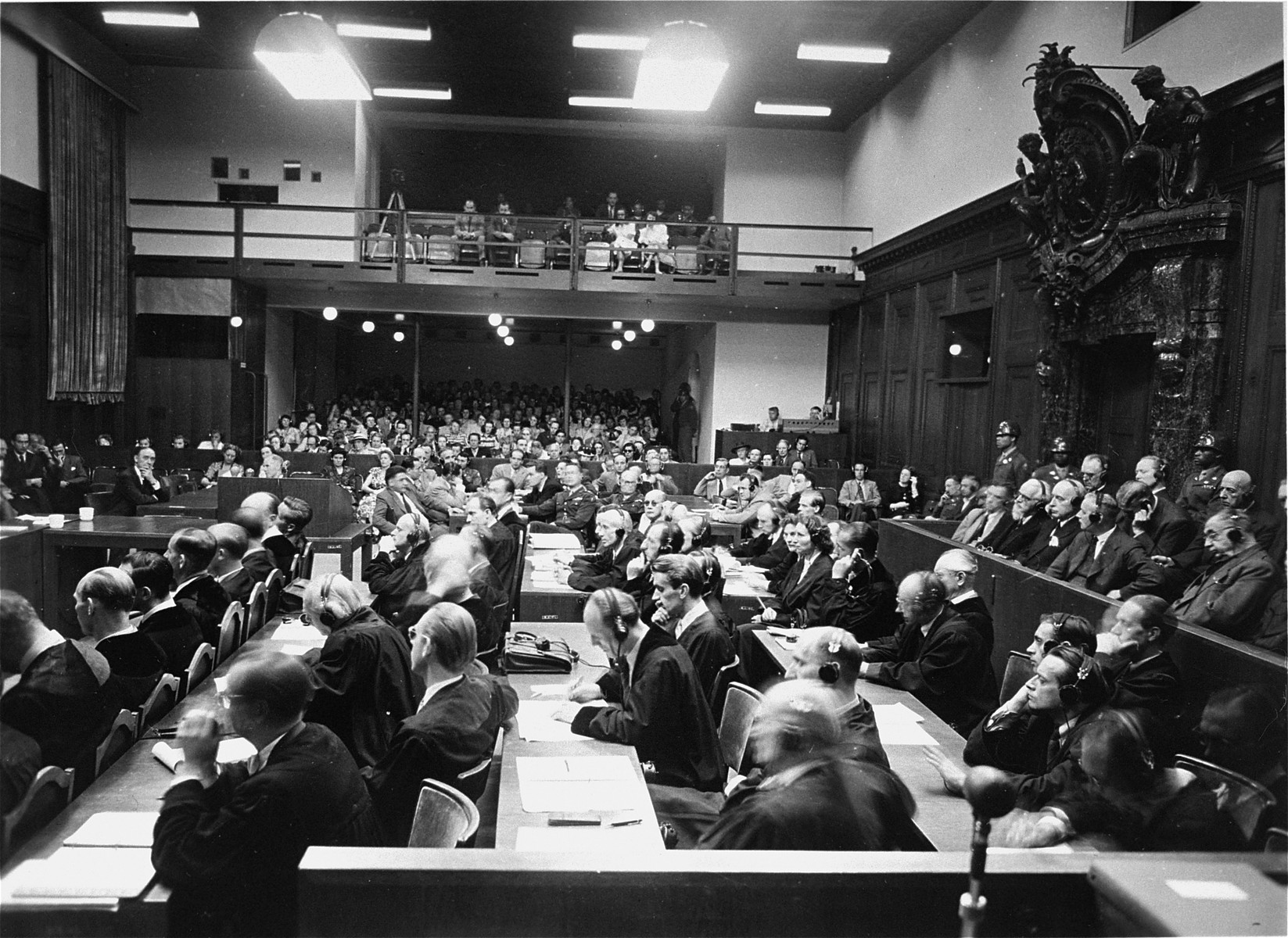 View of the courtroom as seen from the interpreters' section during the I.G. Farben Trial.    The defense lawyers are in front, and the spectators are in the back.