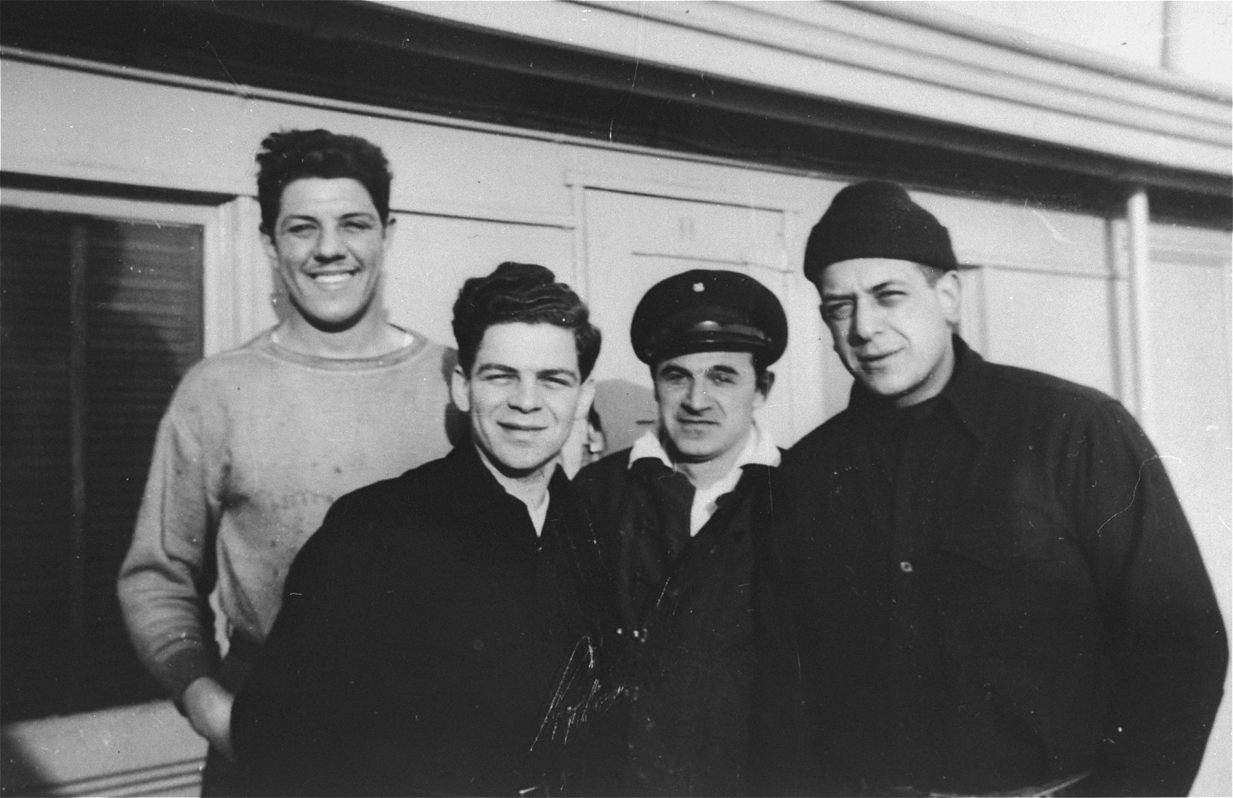 Four crew members of the President Warfield (later the Exodus 1947) pose on the deck of the ship before its departure for Europe.    Pictured from left to right are: William Millman, Avi Livney, Michael Weiss and Cyril Weinstein.