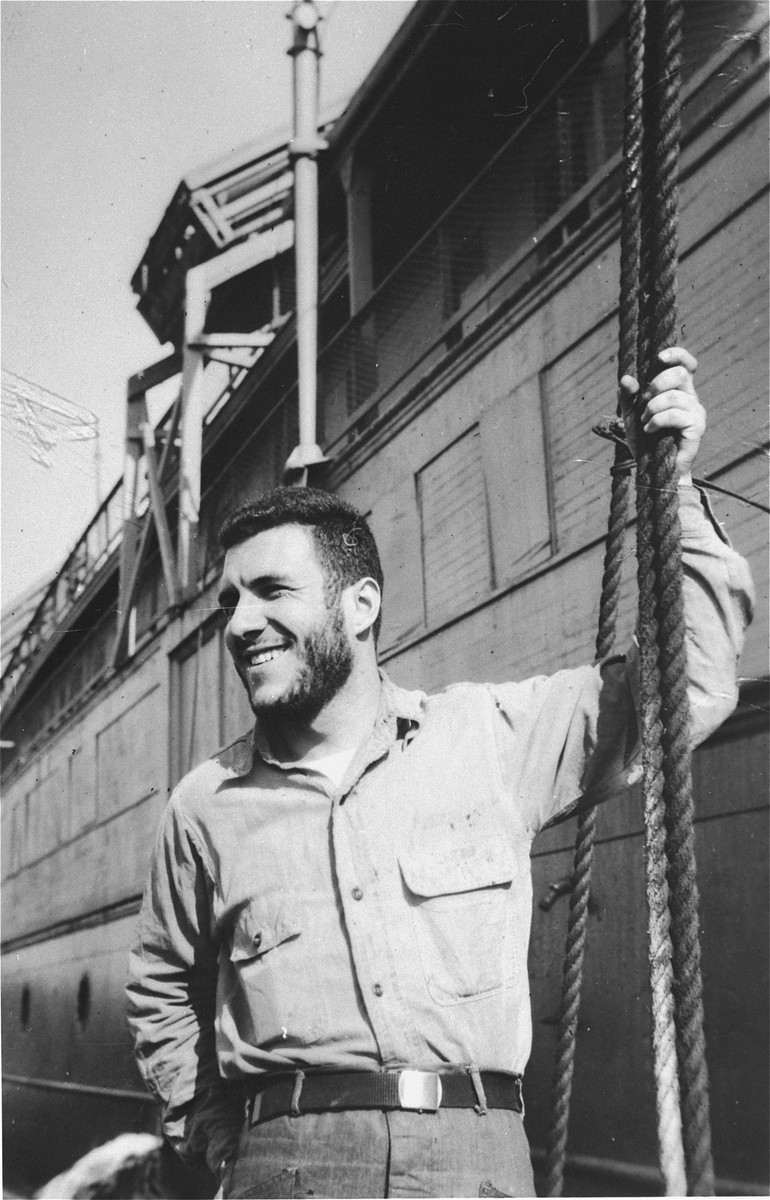 A crew member of the President Warfield (later the Exodus 1947) poses next to the ship in Baltimore harbor.  Pictured is David Millman from Philadelphia.