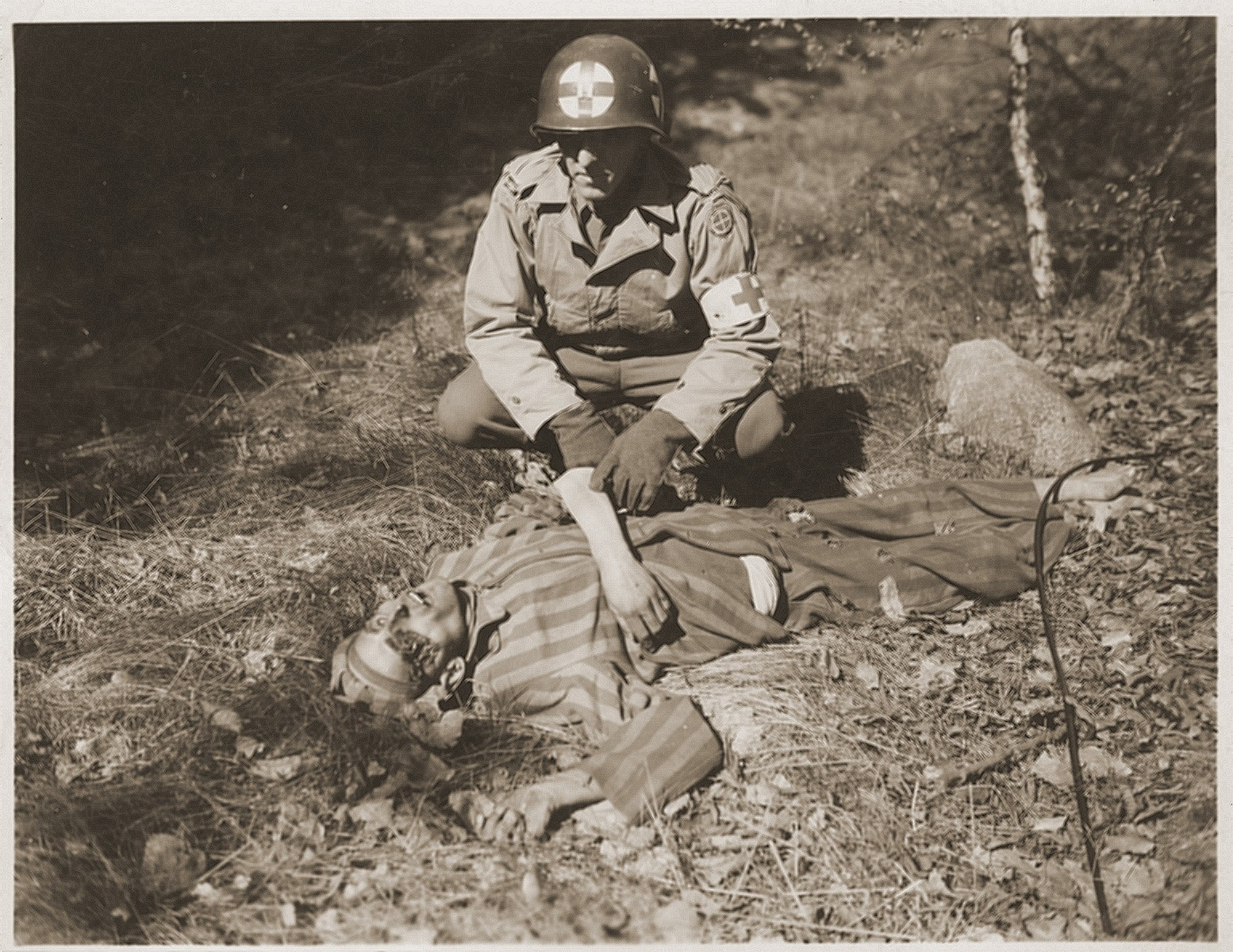 An American soldier kneels by the corpse of a prisoner on the roadside near Gardelegen.  The prisoner was shot by the SS when he was too exhausted to continue on a death march from the nearby town of Mieste.