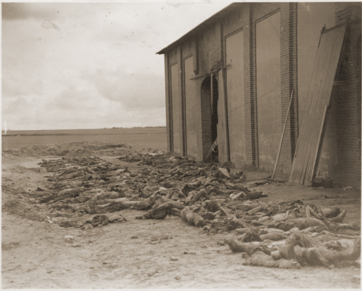 """The bodies of concentration camp prisoners killed by the SS lie outside of a barn near Gardelegen.    The original caption reads """"German civilians bury victims of Nazi sadism.  The charred bodies of victims of Nazi brutality lie waiting for their reburial by civilians [from] nearby Gardelegen, Germany."""""""