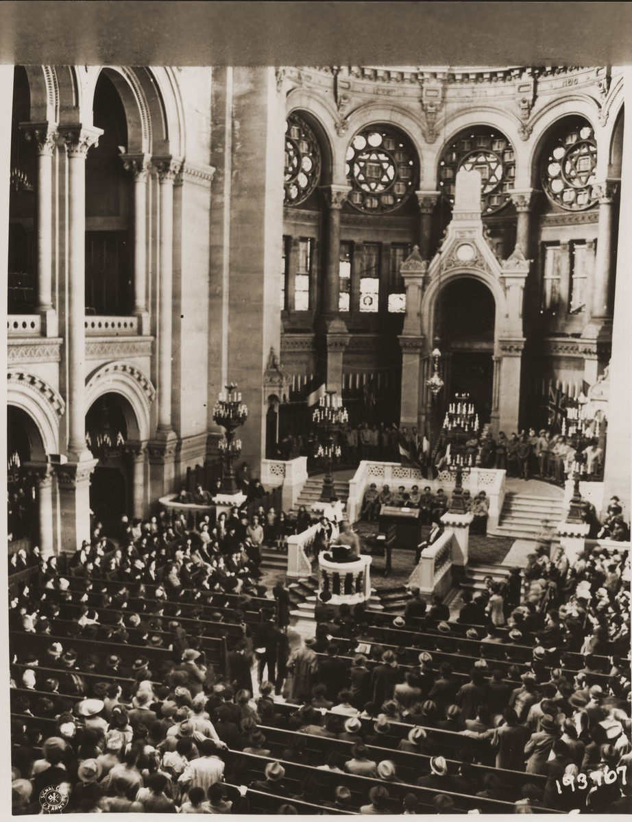 Rabbi Judah Nadich, chief Jewish chaplain for the American army in Europe, delivers a speech to French civilians and Jewish soldiers at the rue de la Victoire synagogue in Paris.