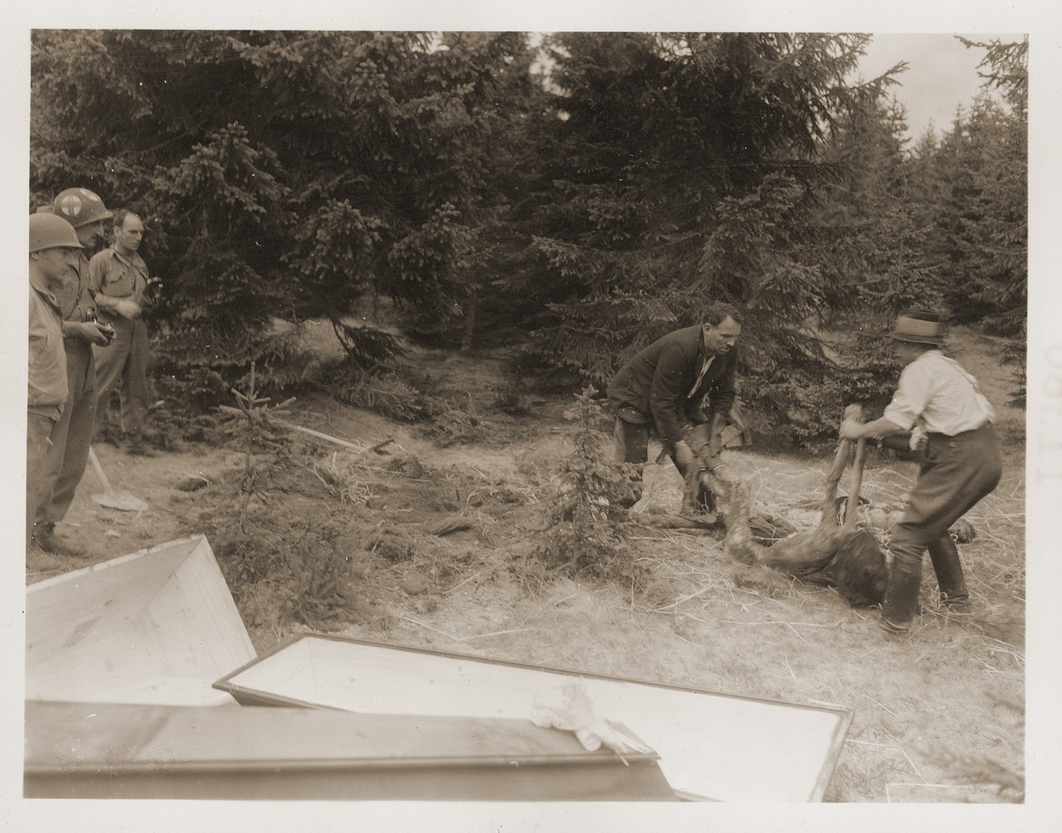Under the supervision of American soldiers, German civilians pull a body from a  mass grave containing the corpses of Jewish women who died at the end of a death march from Helmbrechts, a sub-camp of Flossenbuerg.