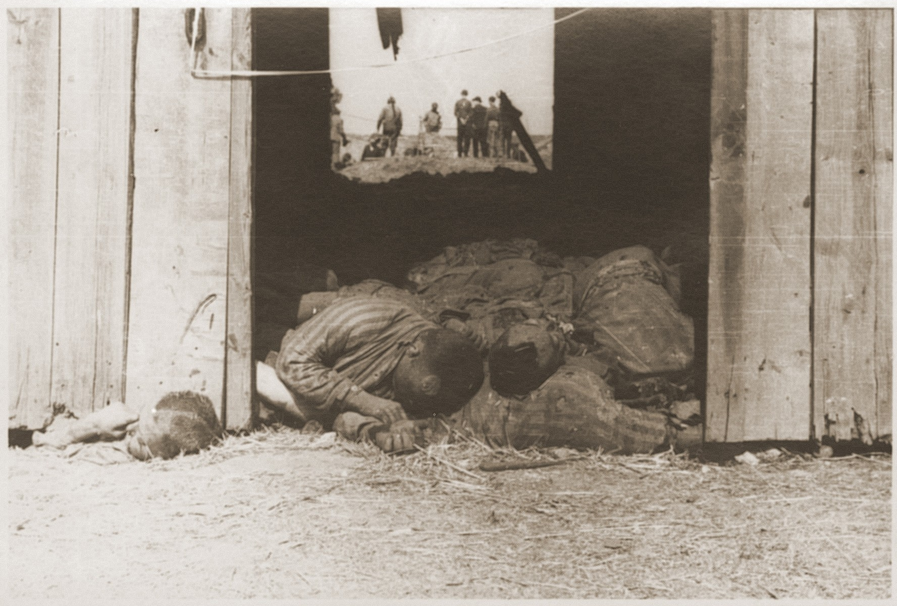 The bodies of concentration camp prisoners killed by the SS in a barn outside of Gardelegen.  In the background American soldiers inspect the barn.