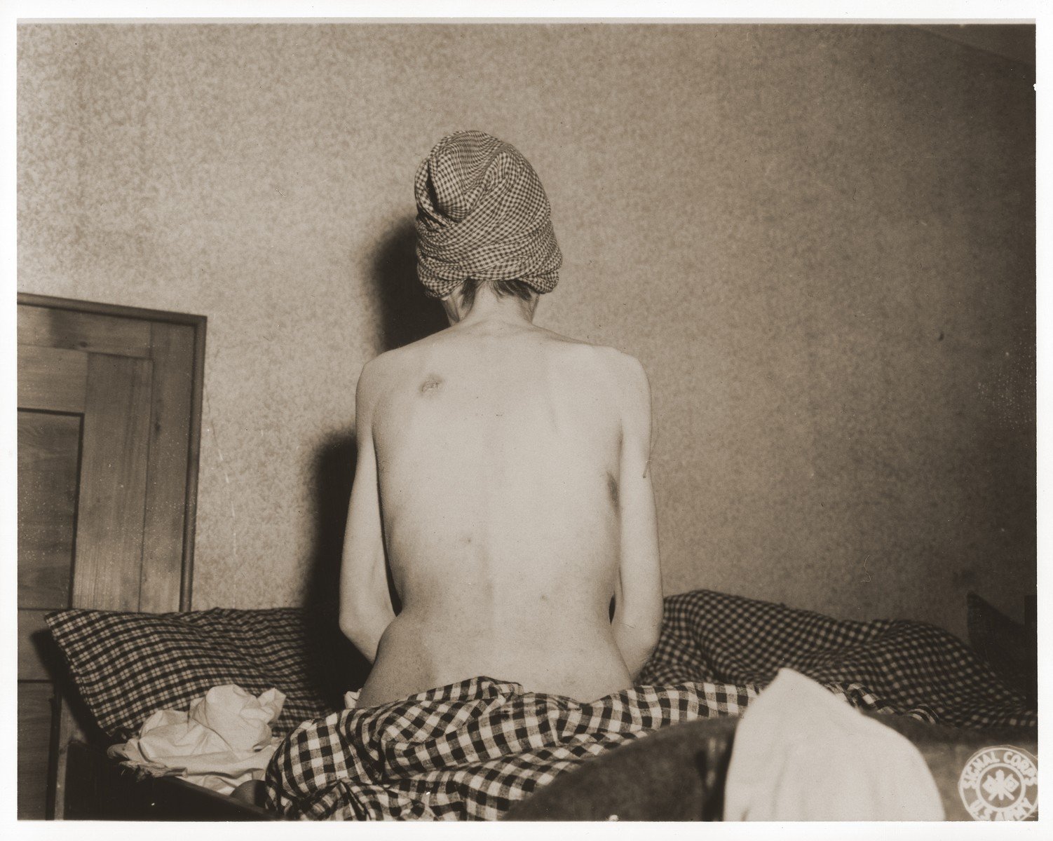 An emaciated female Jewish survivor of a death march sits up in bed at an American military field hospital in Volary, Czechoslovakia.  Pictured is nineteen year old Marika Roth.