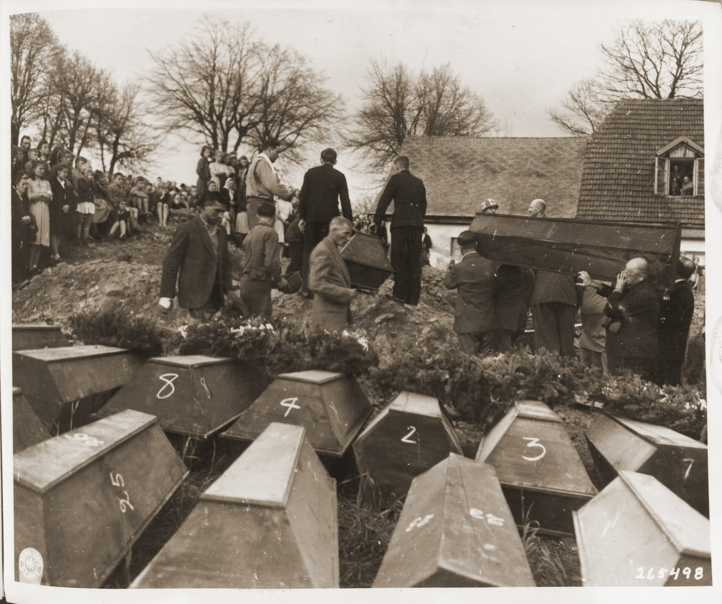 German civilians from Volary attend burial services for the Jewish women exhumed from a mass grave in the town.  The victims died at the end of a death march from Helmbrechts, a sub-camp of Flossenbuerg.