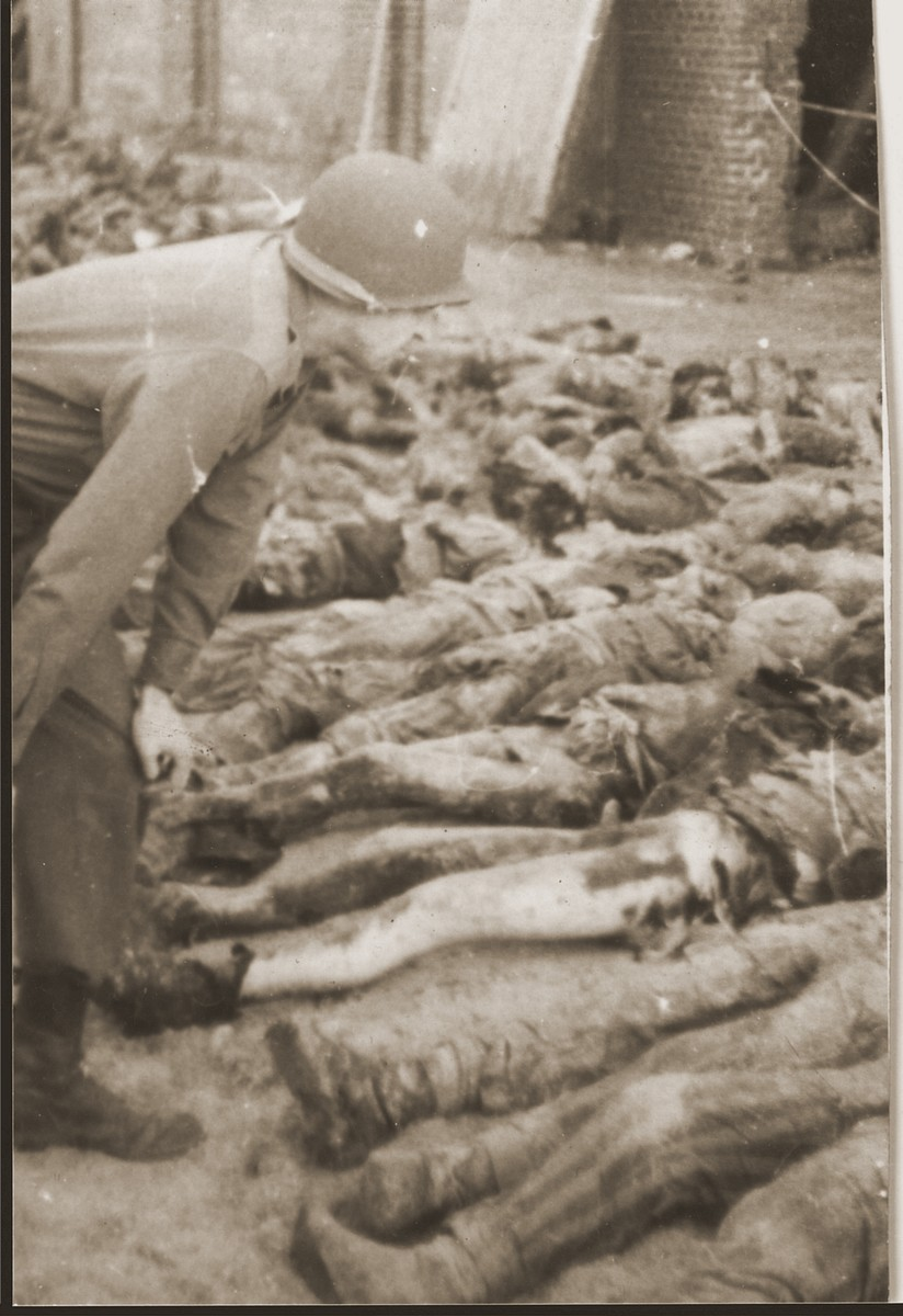 An American soldier examines the corpses of prisoners killed by the SS in a barn near Gardelegen.