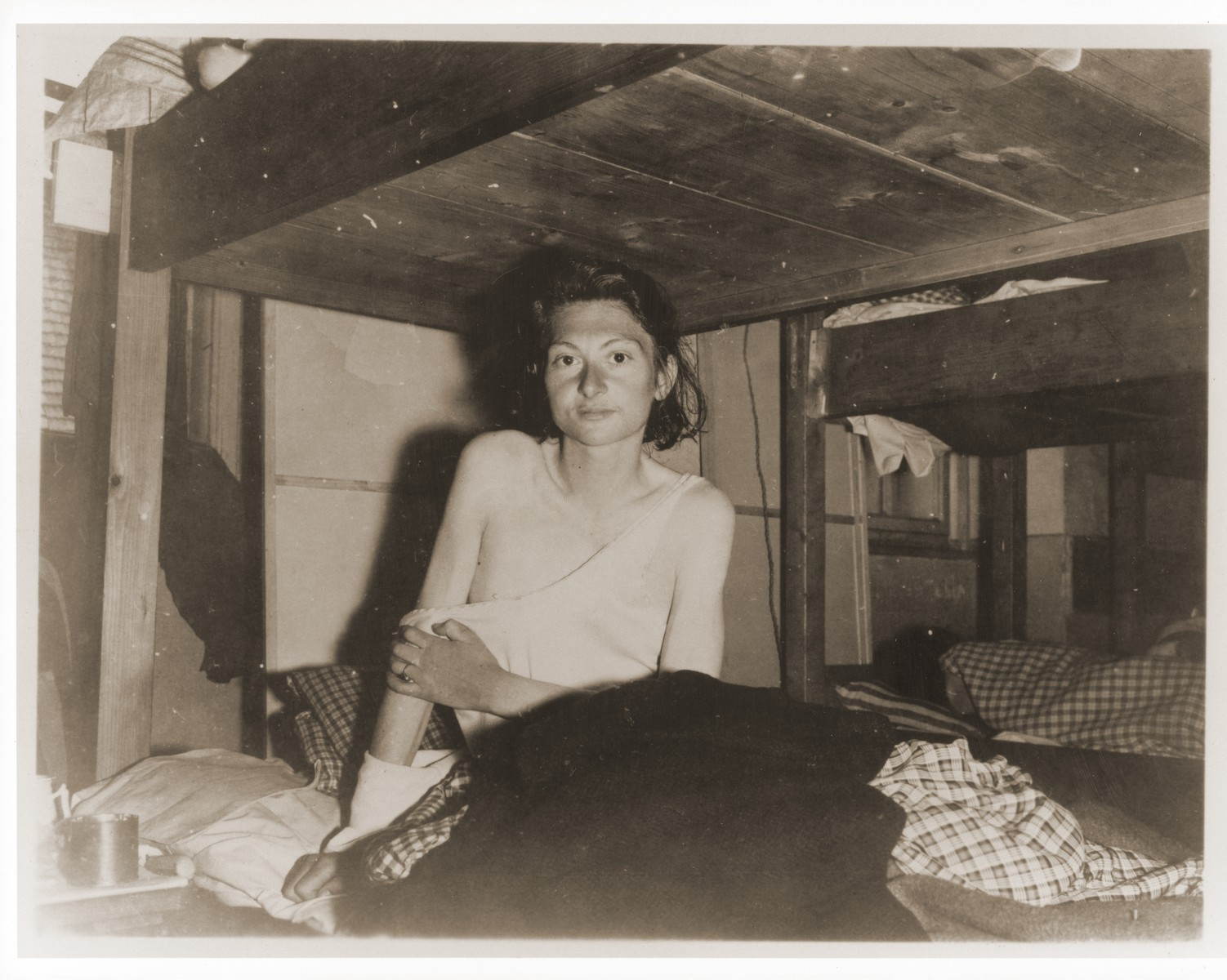 "An emaciated female Jewish survivor of a death march sits up in bed at an American military field hospital in Volary, Czechoslovakia.  Pictured is twenty-two year old Amalie Mary Reichmann.   The original caption reads ""Before and After Enslavement: Weakened by malnutrition after a forced march of 30 days during Nazi enslavement, this unidentified girl was found in Volary, Czechoslovakia, by units of the 5th Division, U.S. Third Army.  She was in a group of 150 persons, twenty of whom died daily  during the march."""