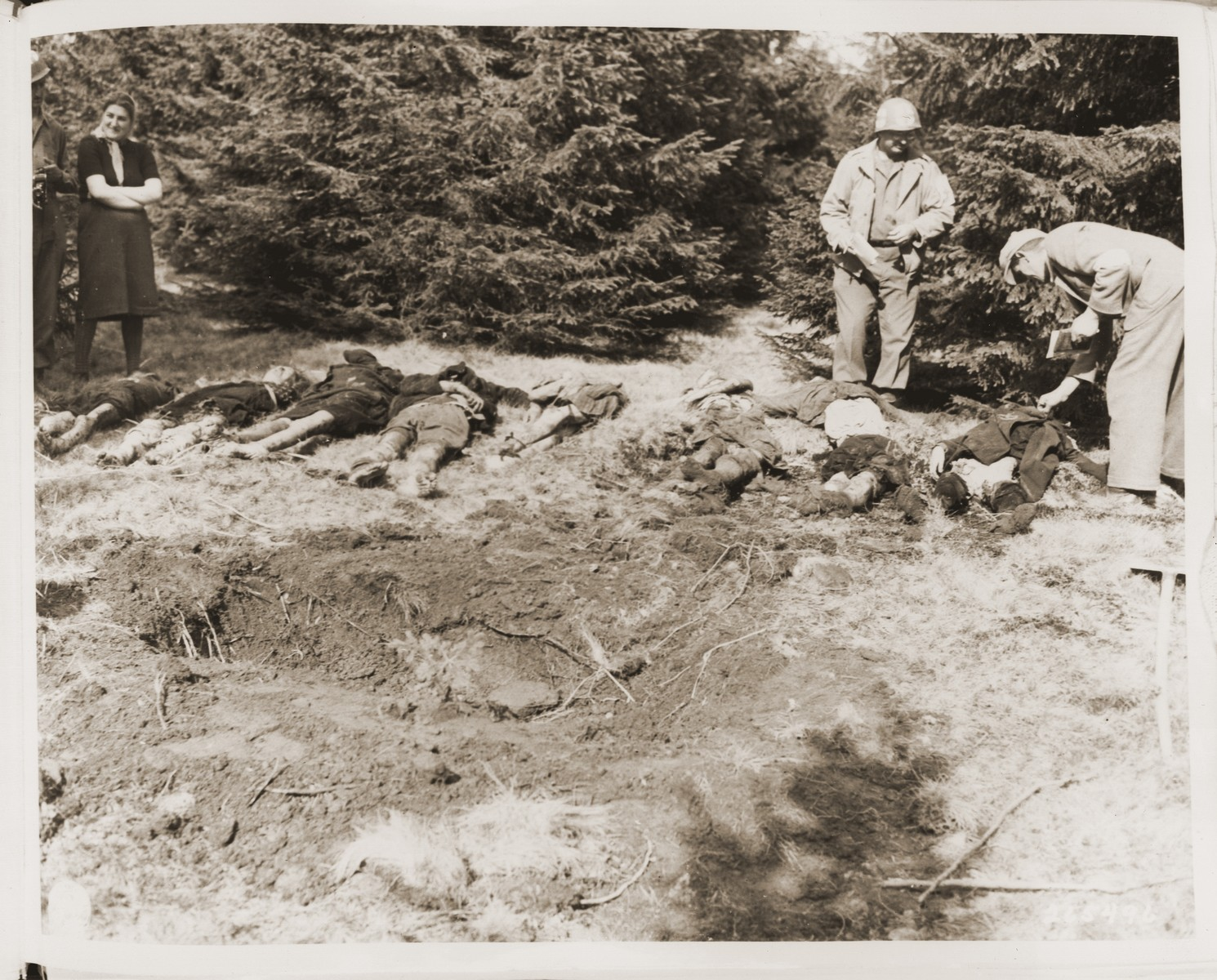 A medic with the 5th Infantry Division, 3rd U.S. Army, checks the bodies of Jewish women exhumed from a mass grave in Volary.  The victims died at the end of a death march from Helmbrechts, a sub-camp of Flossenbuerg.