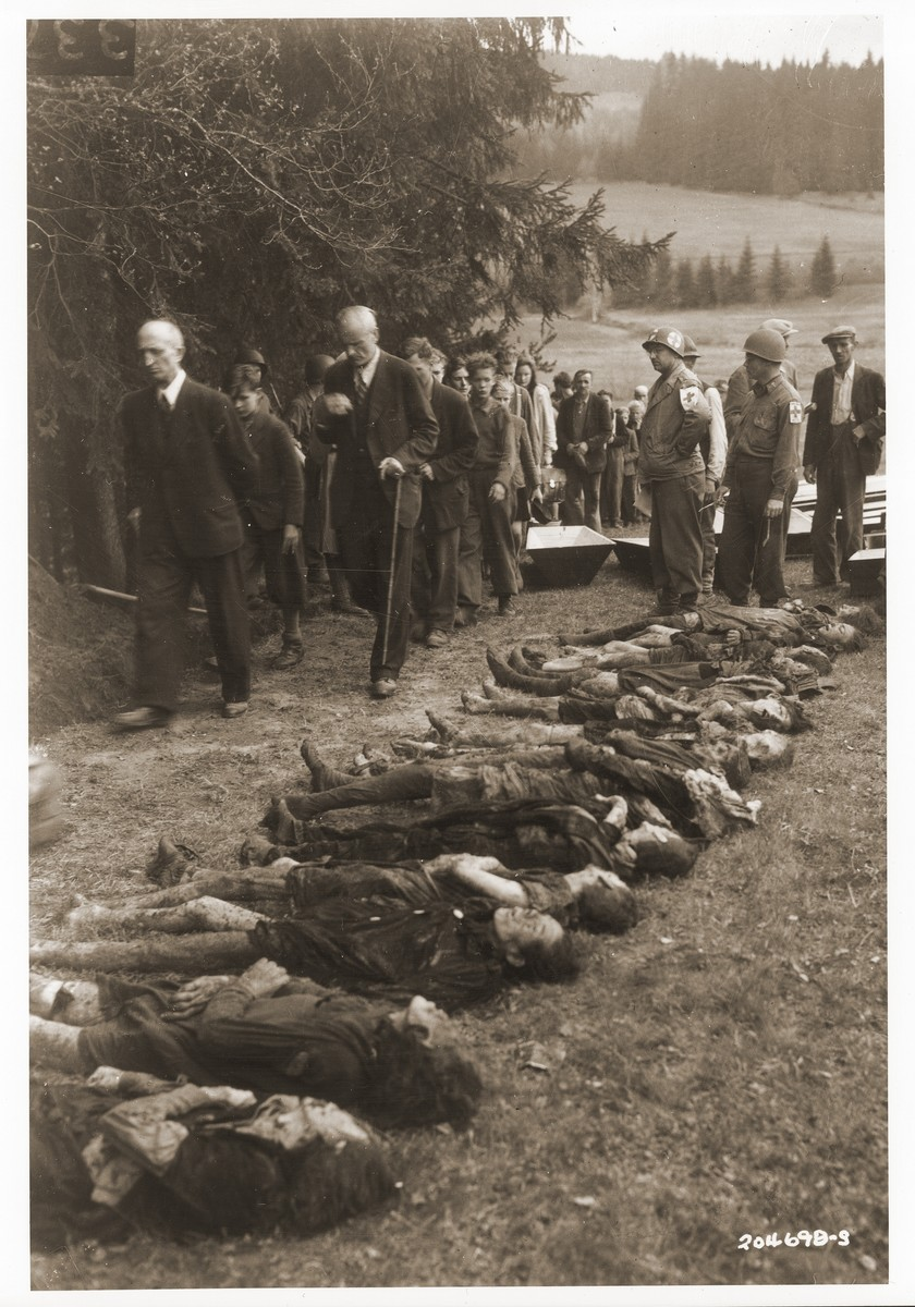 Captain Nathan Knoll and other American medics, supervise German civilians as they file past the bodies of Jewish women exhumed from a mass grave in Volary.  The victims died at the end of a death march from Helmbrechts, a sub-camp of Flossenbuerg.  The 14 year old boy marching in the front is Boris Surm.