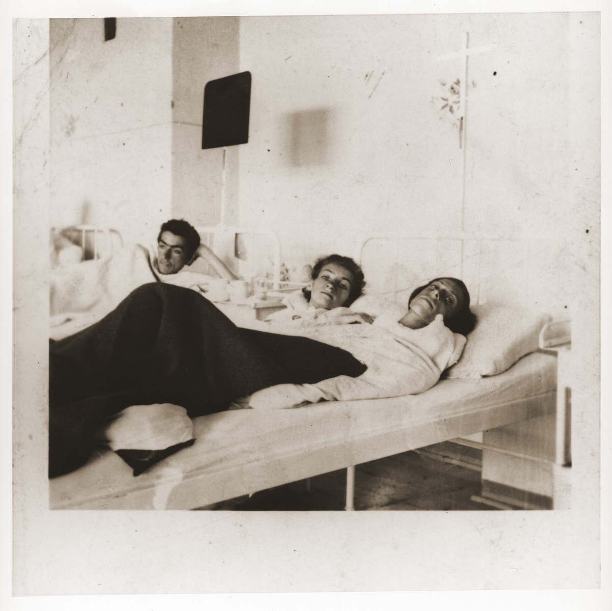 Three Jewish women in a hospital provided by American troops.  The women are survivors of a death march from Helmbrechts that ended in Volary.  Among those pictured is Rozia Epsztajn (center).