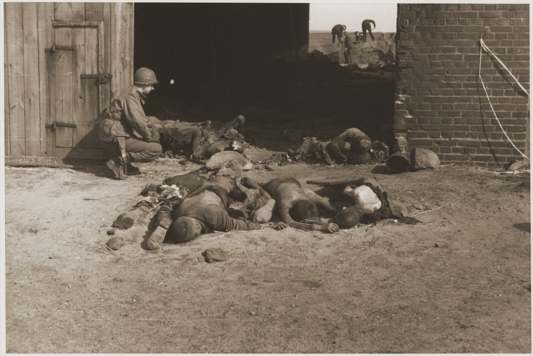 An American soldier kneels beside the charred bodies of prisoners who were burned alive inside a barn near Gardelegen.  In the background, German civilians exhume corpses that were buried in a mass grave by the SS before fleeing the site.