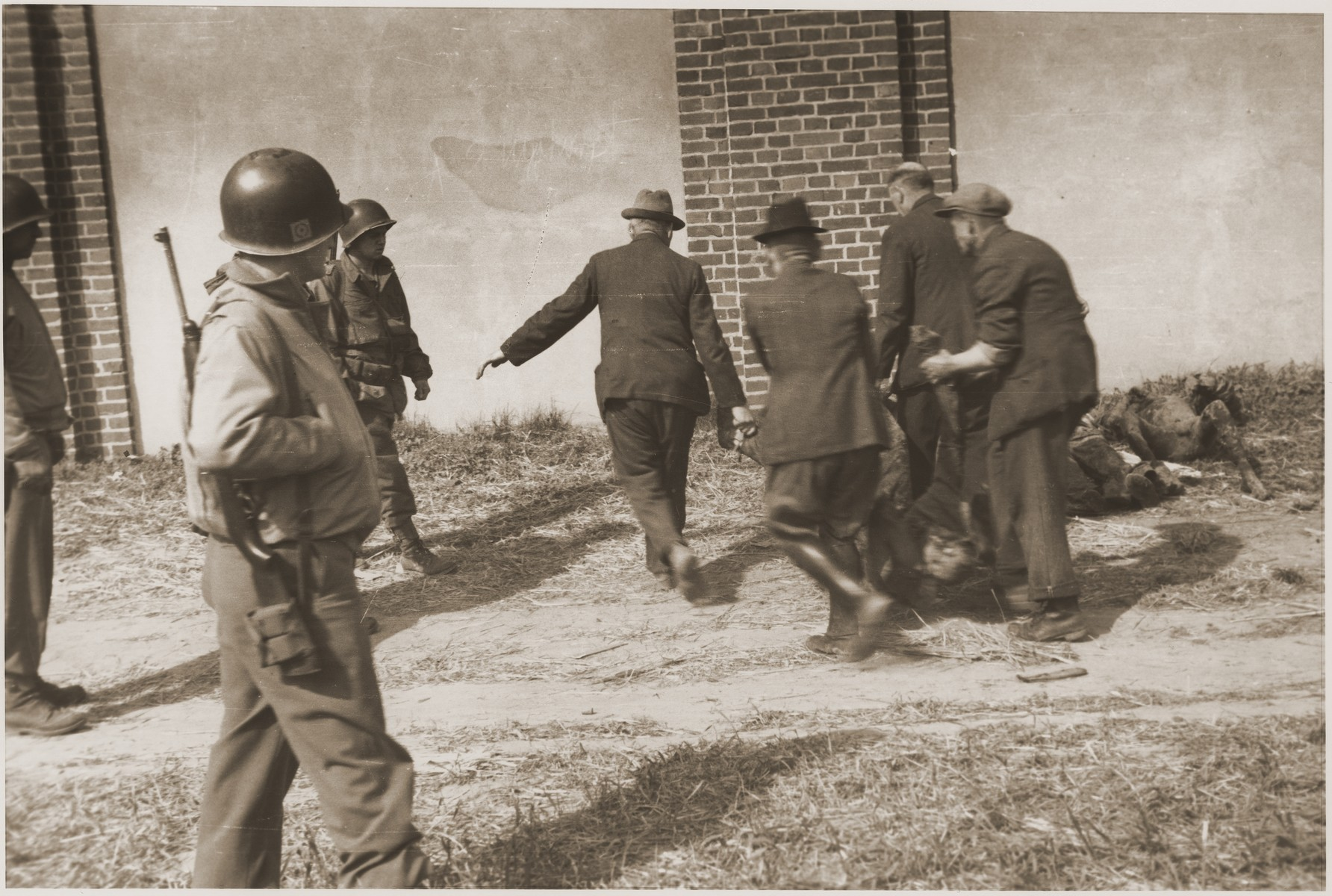 Under the supervision of the Ninth U.S. Army, German civilians are forced to remove the charred corpses of prisoners from a barn outside of Gardelegen for burial in mass graves.