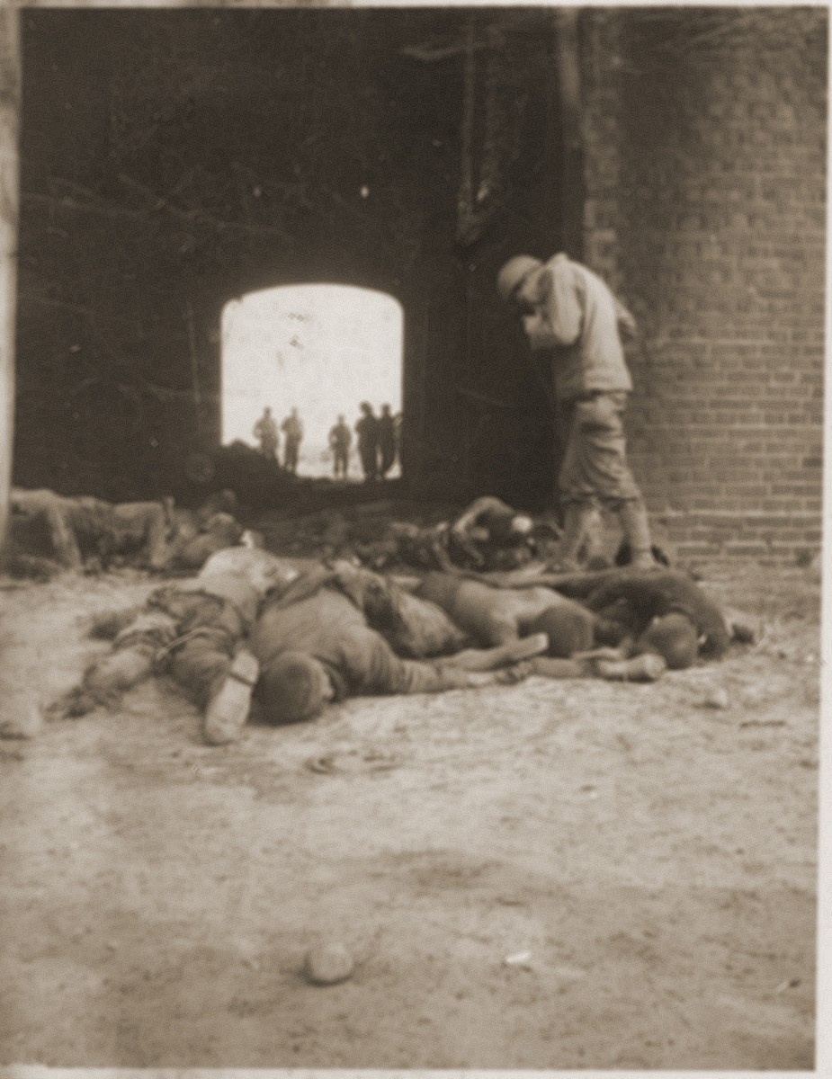 An American soldier photographs the bodies of concentration camp prisoners killed by the SS in a barn outside of Gardelegen.