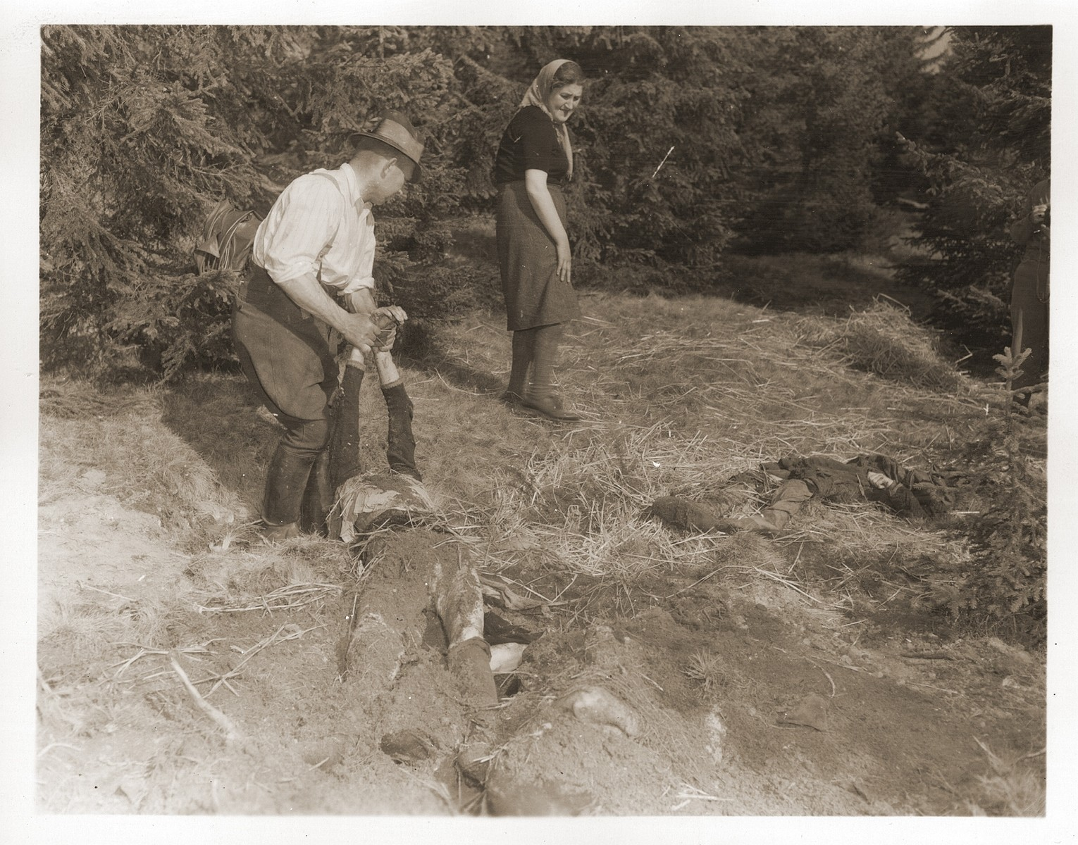 A German civilian exhumes a mass grave near Volary containing the bodies of Jewish women who died at the end of a death march from Helmbrechts, a sub-camp of Flossenbuerg.  The woman, Mina Singer, is a survivor of the march, and was the oldest of the group.