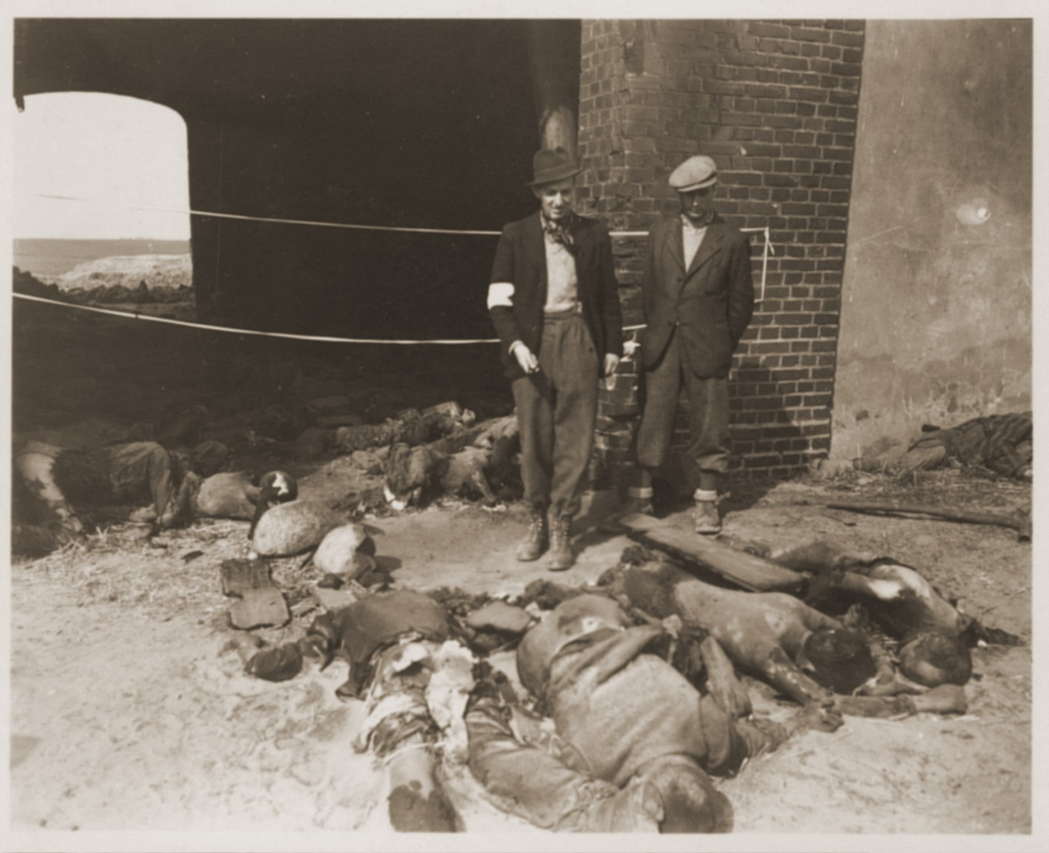 German civilians from Gardelegen stand beside the bodies of concentration camp victims killed by the SS in a barn outside of the town.