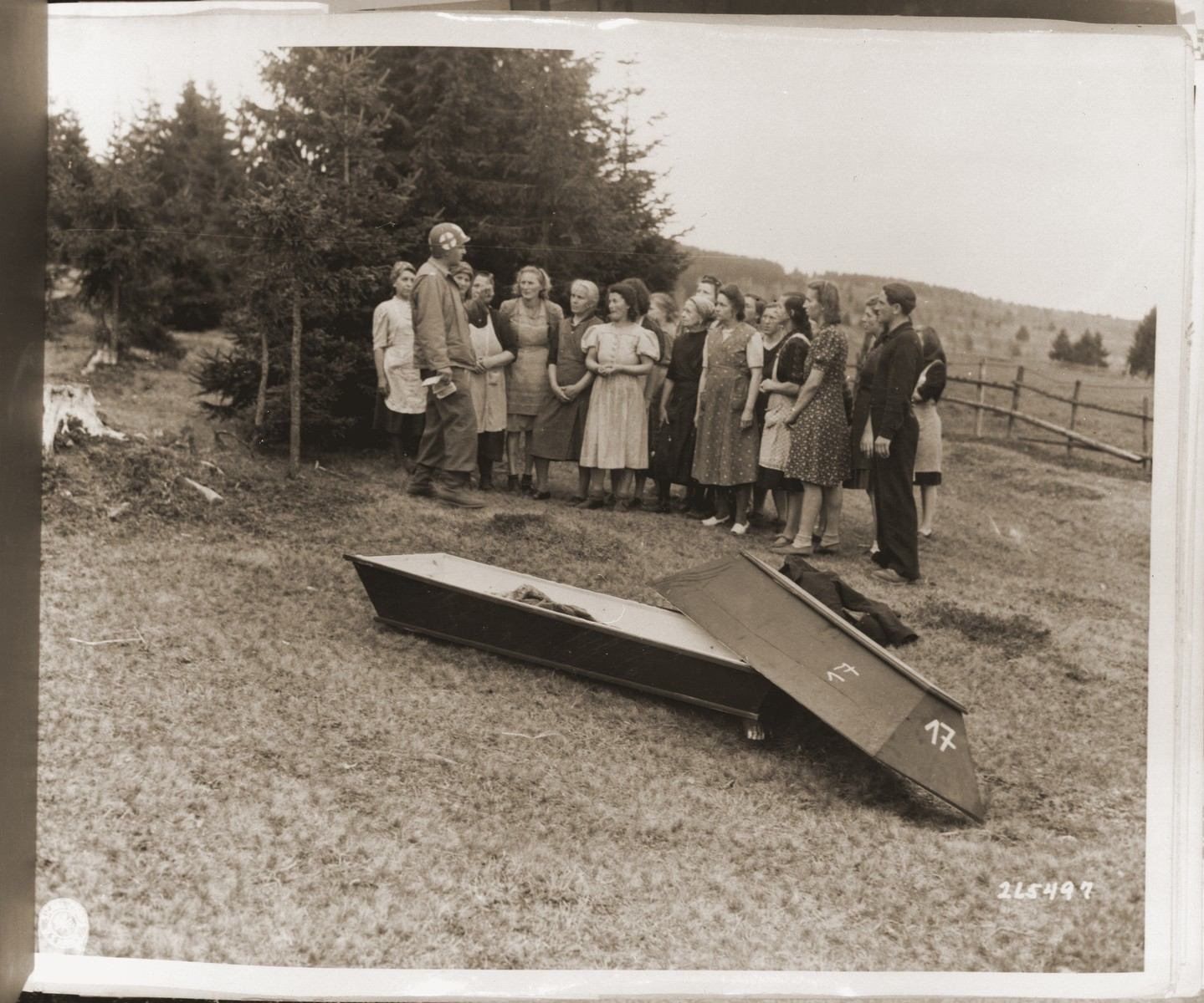 German civilians look at the bodies of Jewish women exhumed from a mass grave in Volary.  The victims died at the end of a death march from Helmbrechts, a sub-camp of Flossenbuerg.