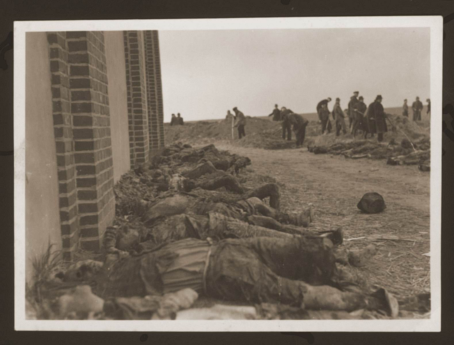 The charred bodies of prisoners burned alive by the SS lie outside of a barn outside of Gardelegen.  In the background German civilians exhume bodies buried in a mass grave by the SS.