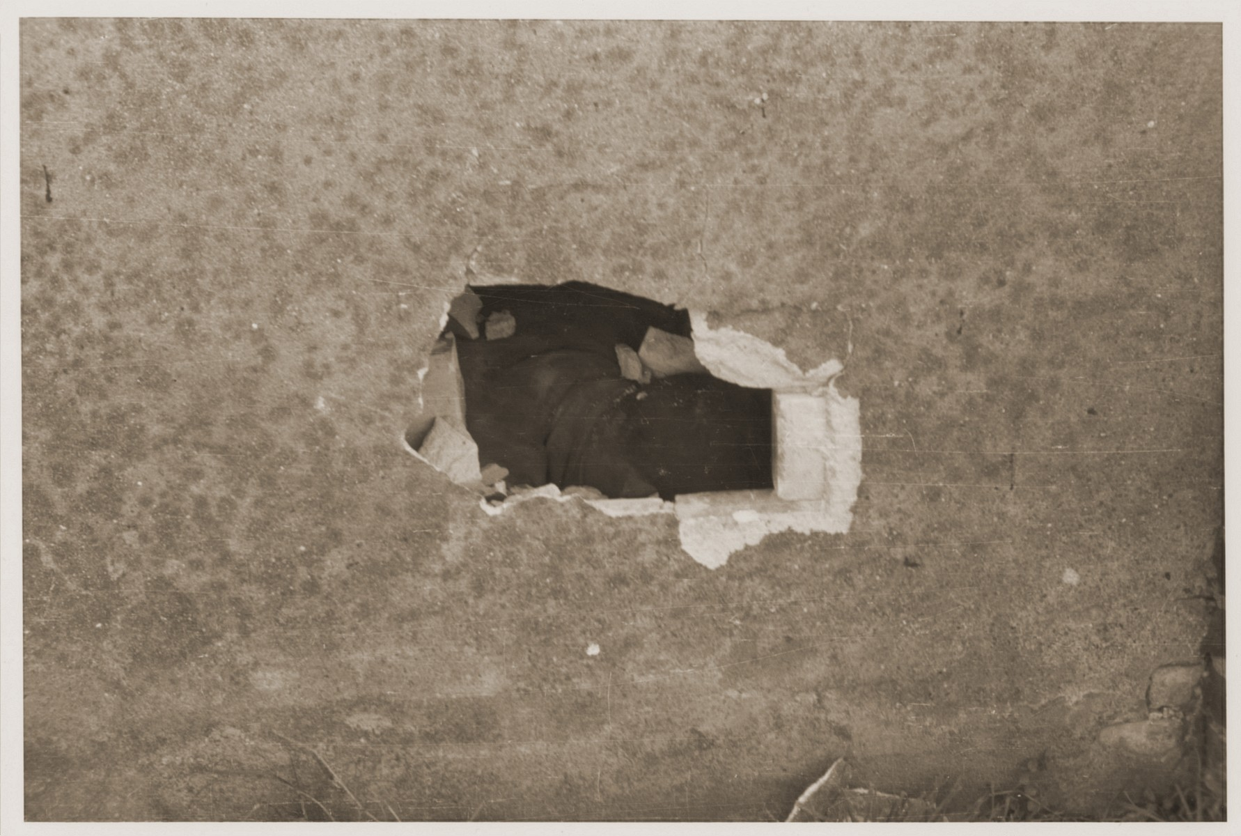 A hole in the barn wall through which the SS and their cohorts shot prisoners kept inside.
