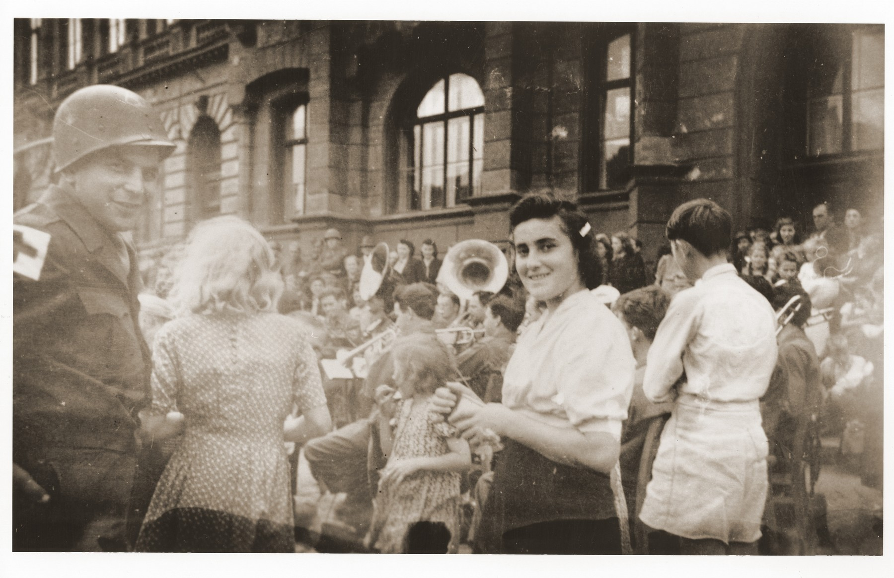 An American medic from the 5th Division, U.S. 3rd Army, and Lilka Haber Silbiger, attend an American soldiers' concert in Prachatice.  The medic participated in the liberation of Lilka and approximately 150 others from a 500 km. death march that ended in Volary.  Facing the camera is Lilly Silbiger (from Oswiecim).