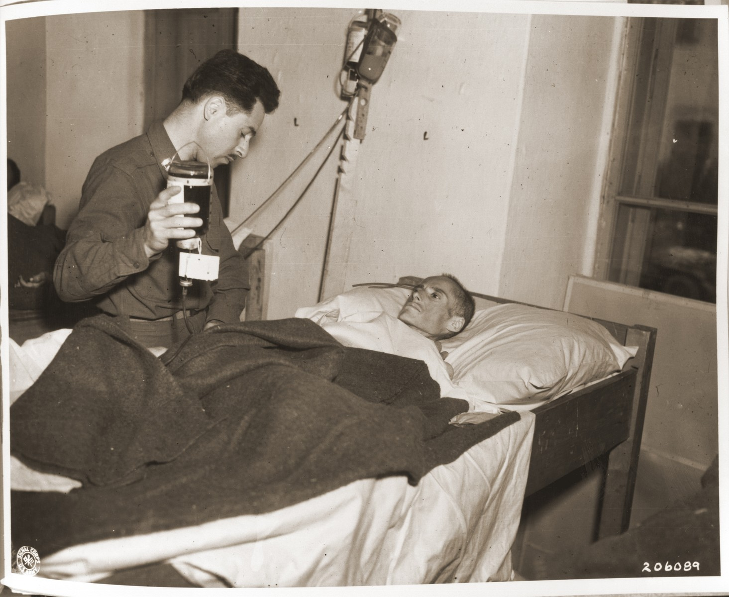 Captain Richard Berman of Philadelphia administers plasma to Roszi Frank, an emaciated survivor of a death march, in an American field hospital in Volary.
