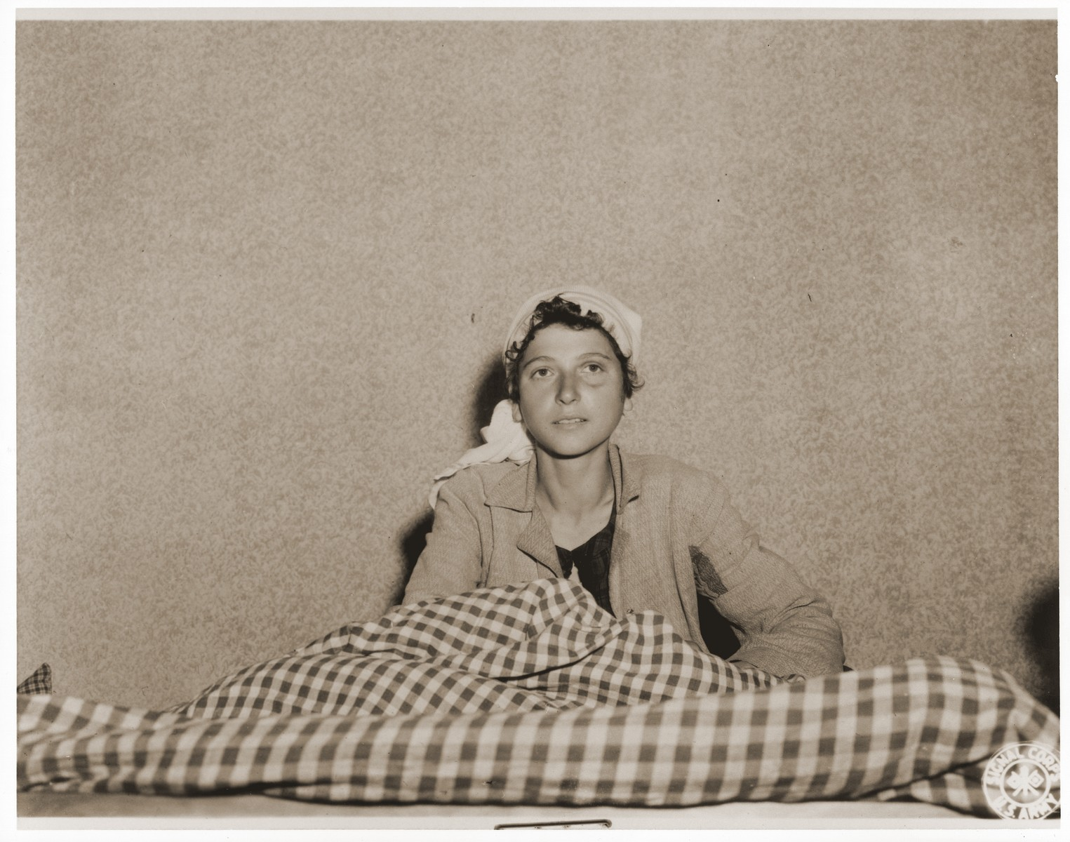 An emaciated female Jewish survivor of a death march sits up in bed at an American military field hospital in Volary, Czechoslovakia.  Pictured is twenty-two year old Gizal Warum.