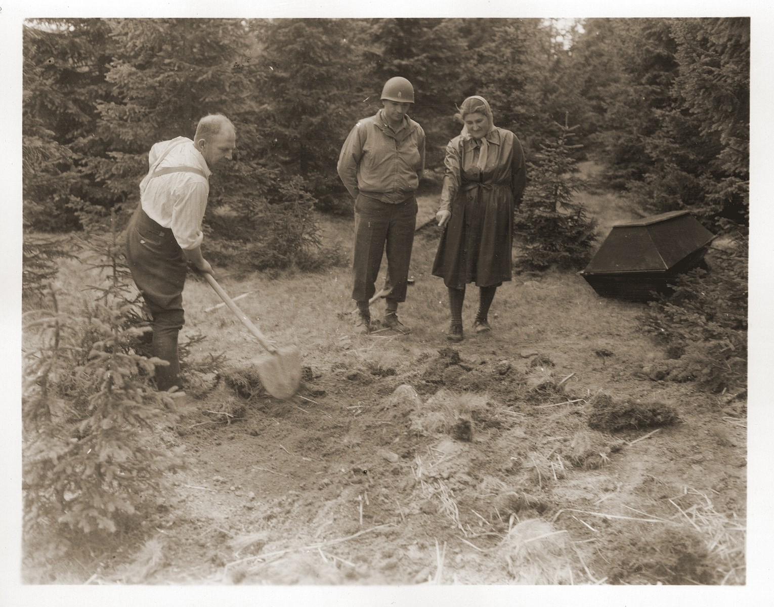 Under the supervision of Jewish chaplain Herman Dicker, 5th Infantry Division, 3rd U.S. Army, a German civilian exhumes a mass grave containing the corpses of Jewish women who died at the end of a death march from Helmbrechts, a sub-camp of Flossenbuerg.  The woman, Mina Singer, is a survivor of the march, and was the oldest of the group.