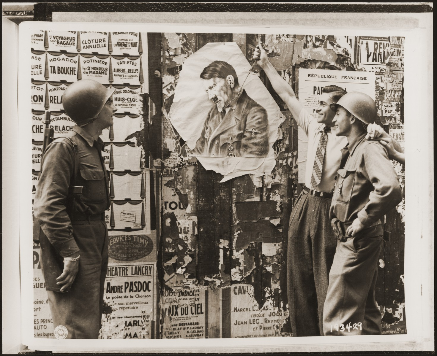 "Two American soldiers watch as a Frenchman ""hangs"" in a portrait of Hitler in effigy."