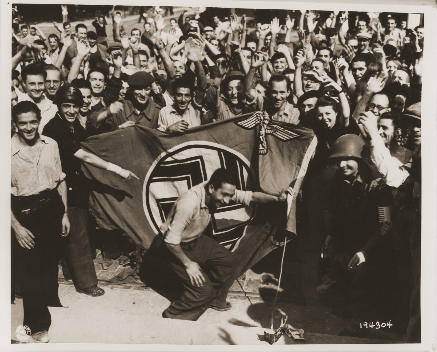 A crowd celebrating the liberation of Marseilles sets fire to a Nazi flag that had been flying over the police building.