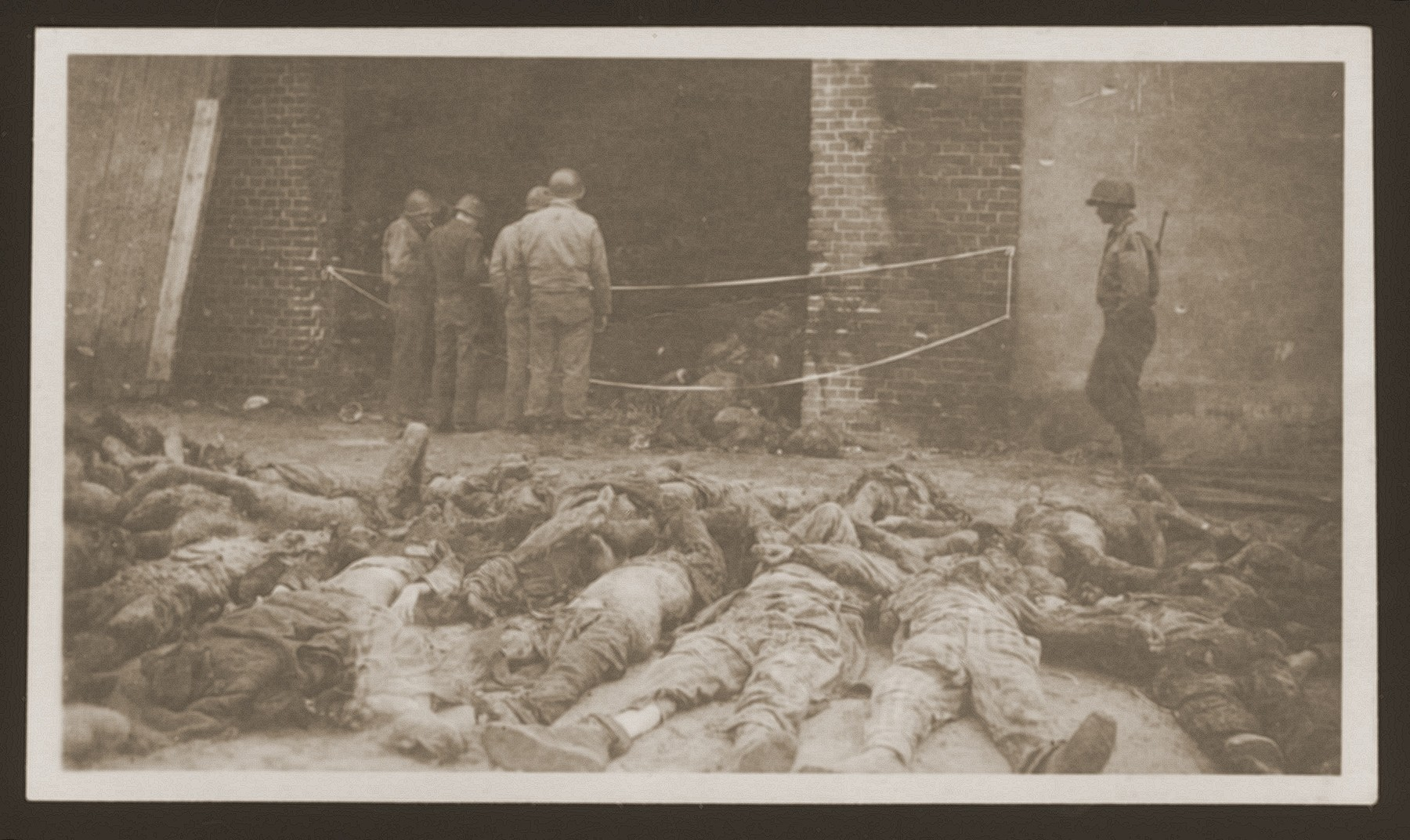 American soldiers look at the charred bodies of prisoners burned alive by the SS in a barn outside of Gardelegen.  In the foreground lie bodies already removed from the barn.