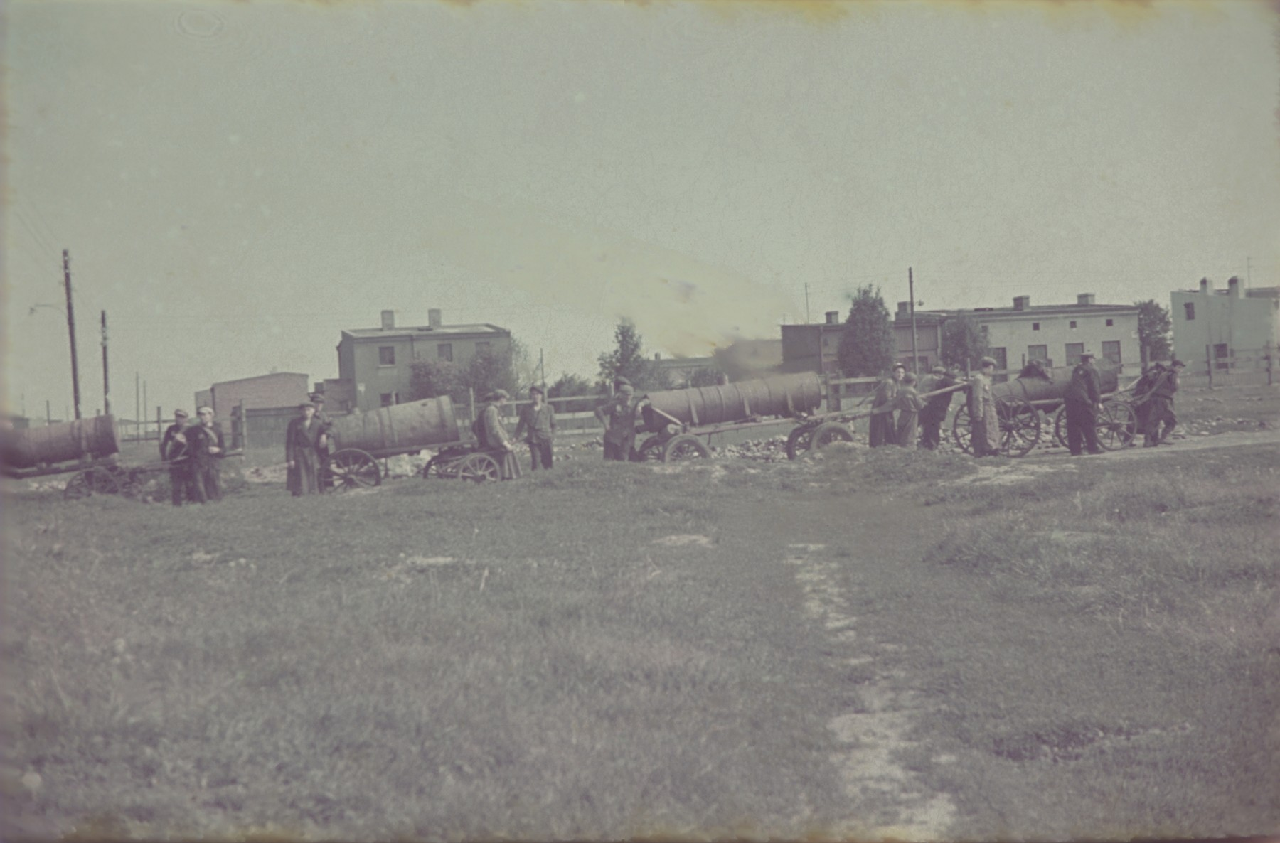 Fecalists haul sewage carts through a field in the Lodz ghetto.