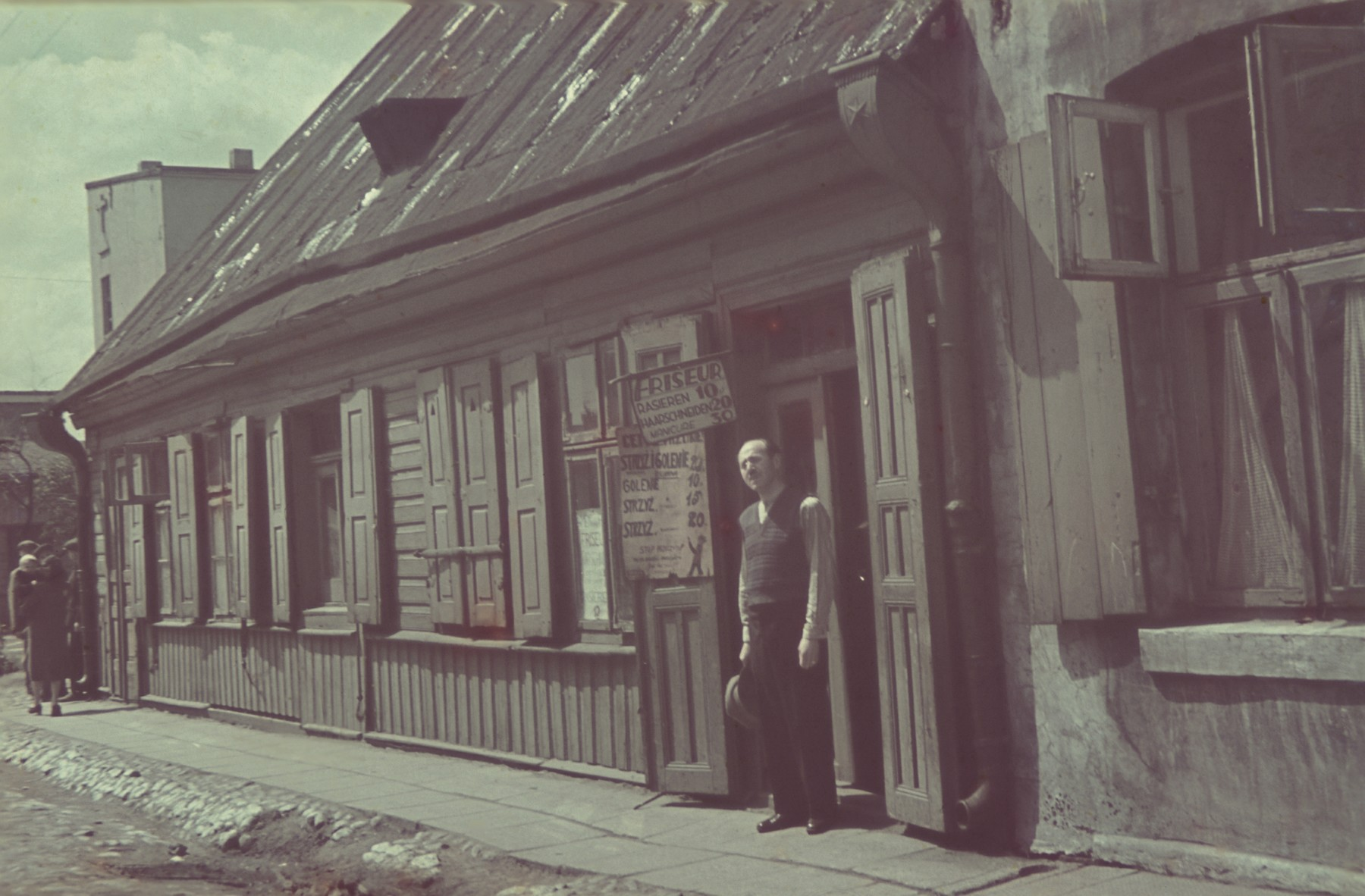 A barber stands outside his shop in the Lodz ghetto.