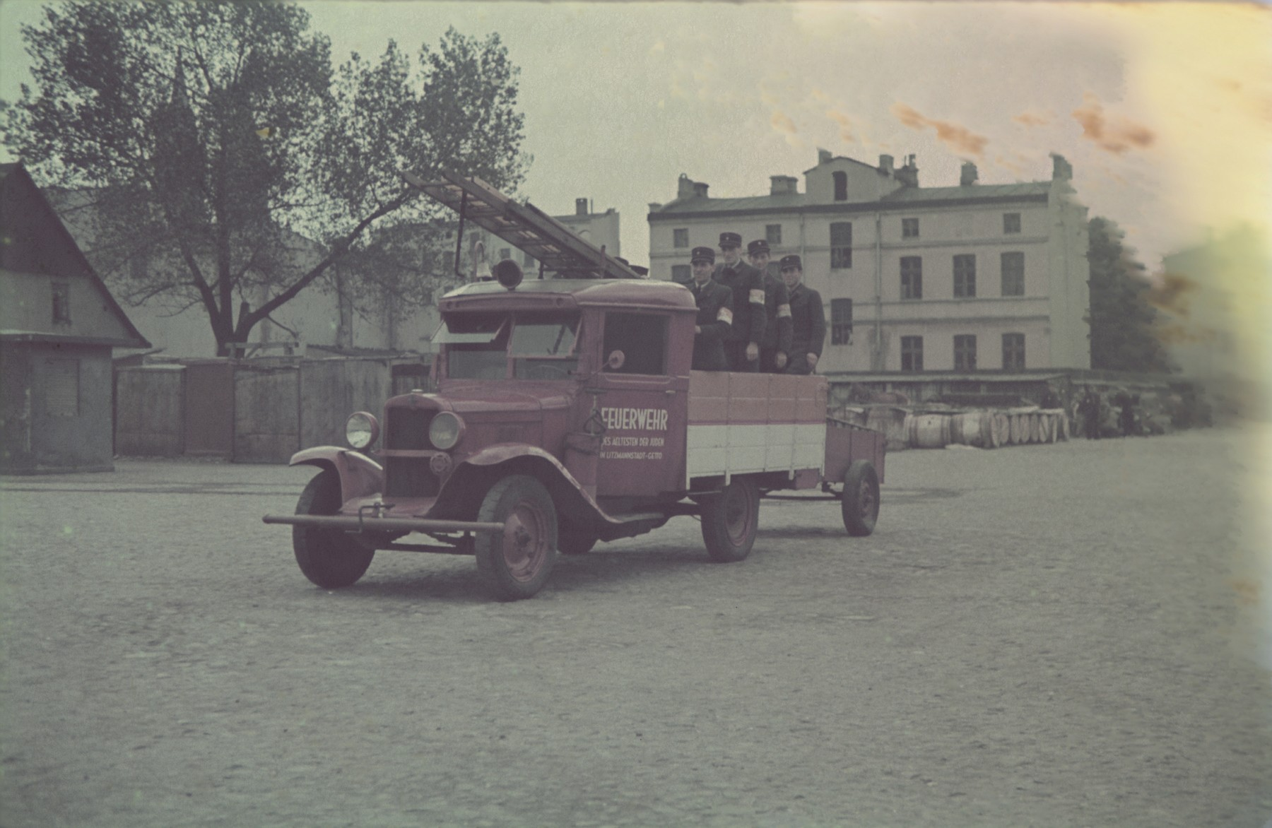Ghetto firefighters ride in the back of a fire truck through the Lodz ghetto.