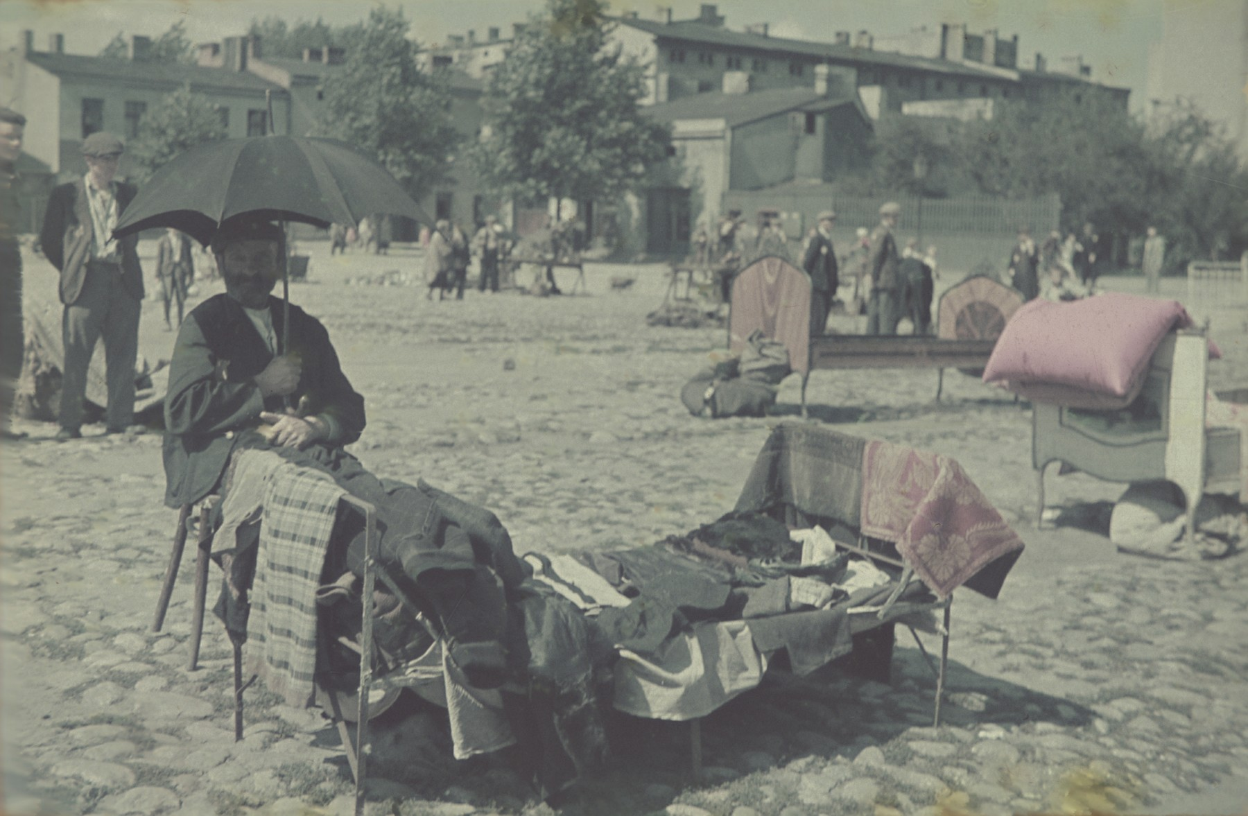 A vendor sits under a shade umbrella in the outdoor market of the Lodz ghetto.