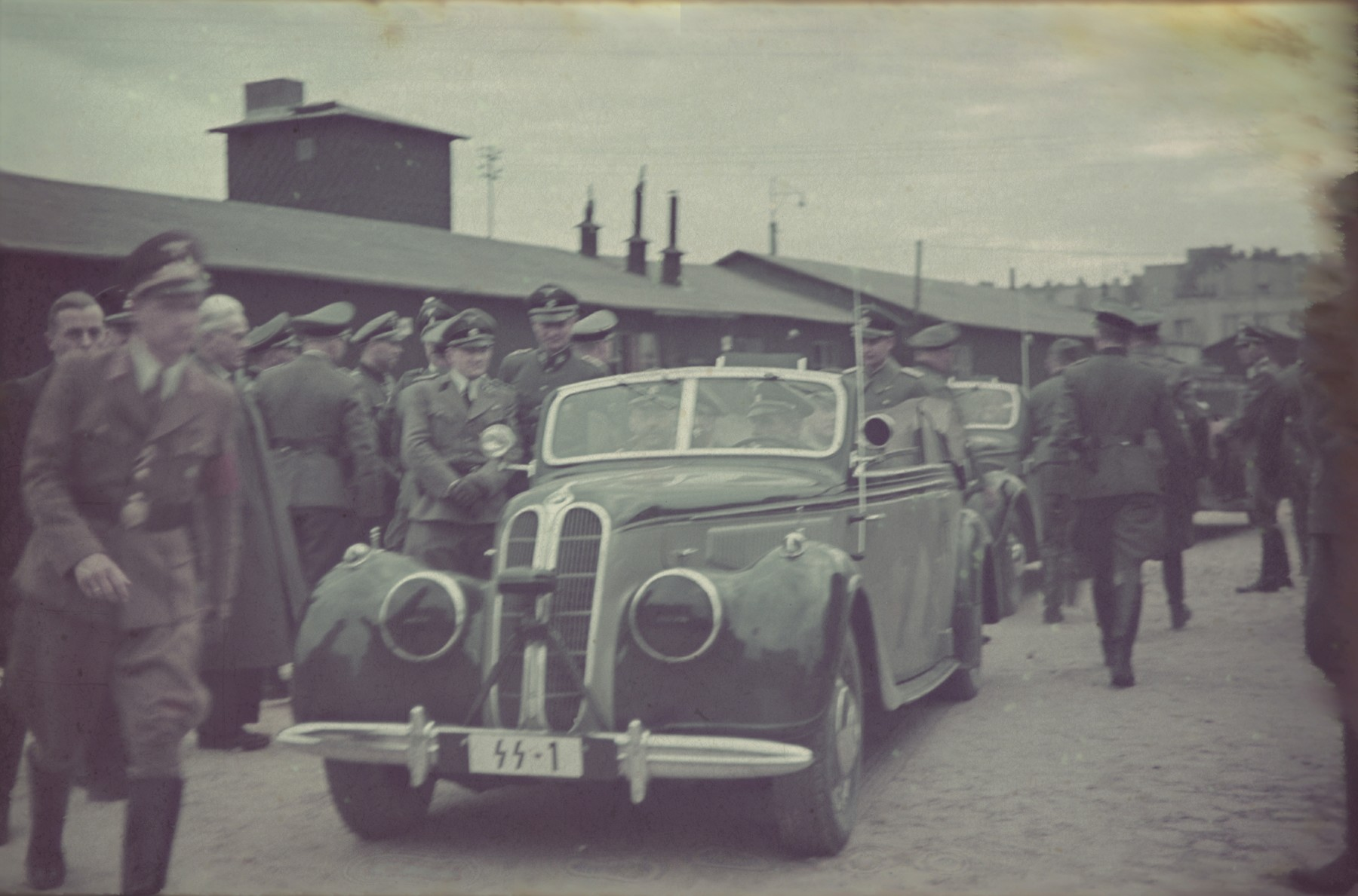 An official visit of Heinrich Himmler in the Lodz Ghetto. Mordechai Chaim Rumkowski, head of the Jewish council, greets the Nazi officials. Standing to the right of the car is Karl Wolff.