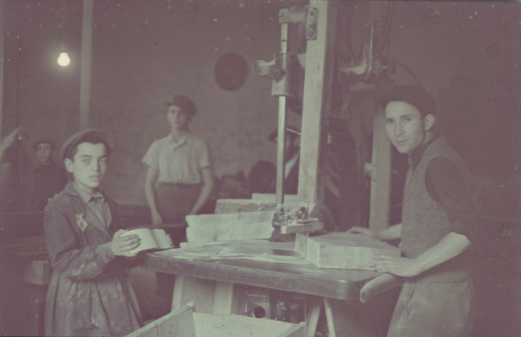 "Jewish youth cut blocks of wood in the furniture workshop in the Lodz ghetto.  Standing  on the right is Daniel Geslewitz and second from the right is Yerszyk Hellmer.  Original German caption: ""Litzmannstadt Getto, Moebelfabrik"" (furniture factory), #11."