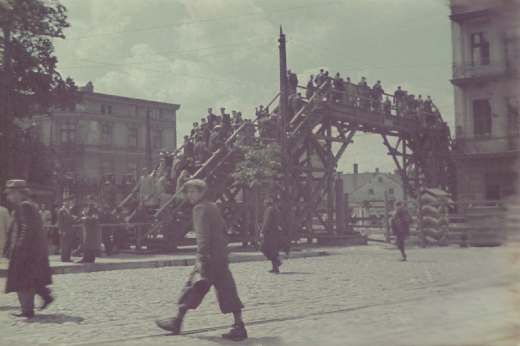 View of Lodz ghetto residents crossing the pedestrian bridge over Zgierska Street at Koscielny Square.