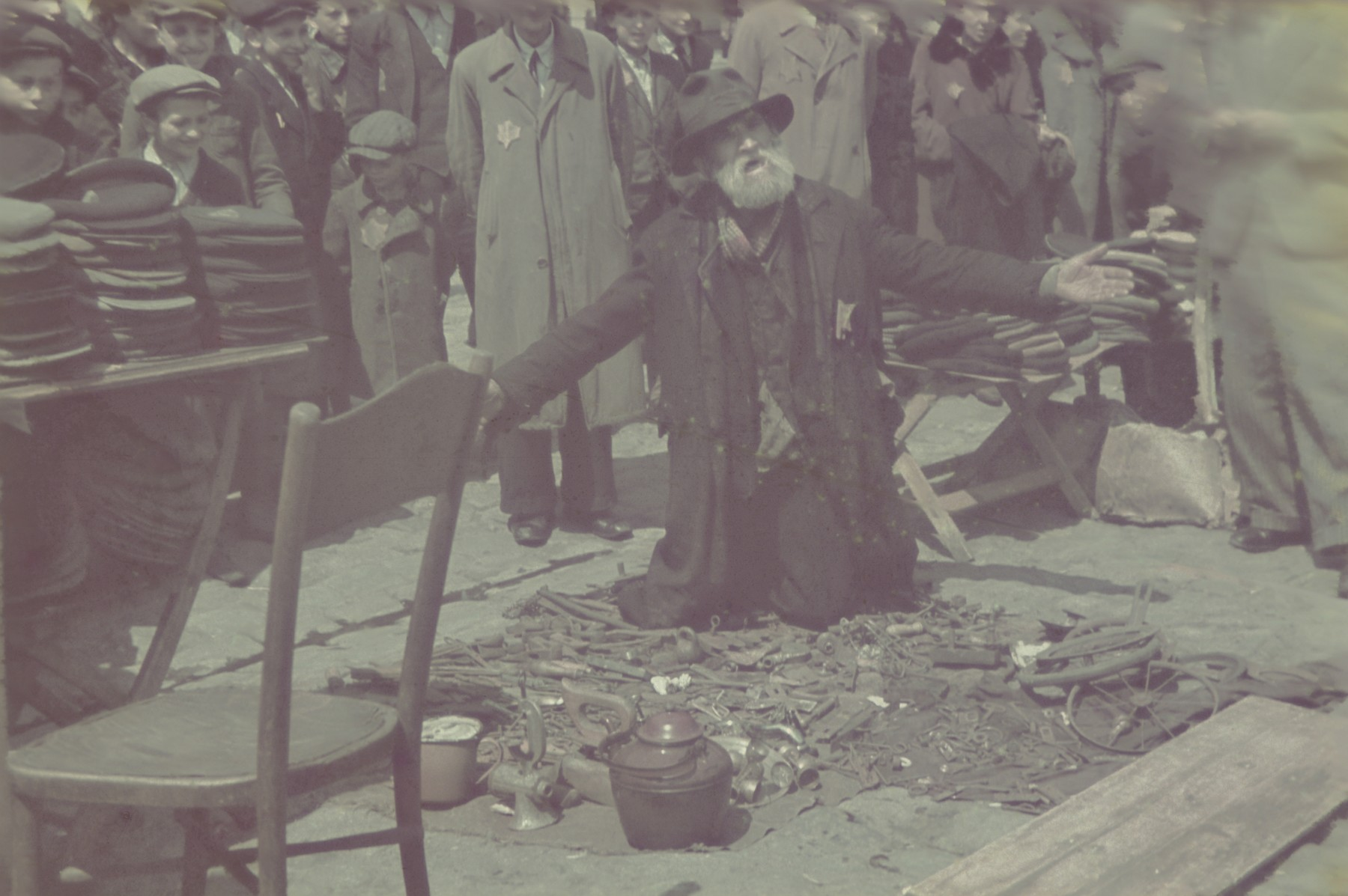 An elderly man at the ghetto market kneels by the objects he is selling with his arms extended .