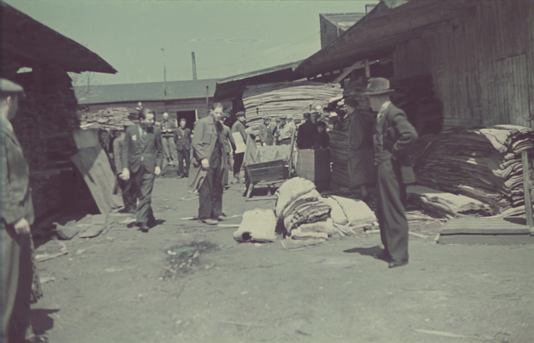 "Workers walk past material stored outside the furniture factory in the Lodz ghetto.  Original German caption: ""Getto, Litzmannstadt, Moebelfabrik"" (furniture factory), #171, 217."