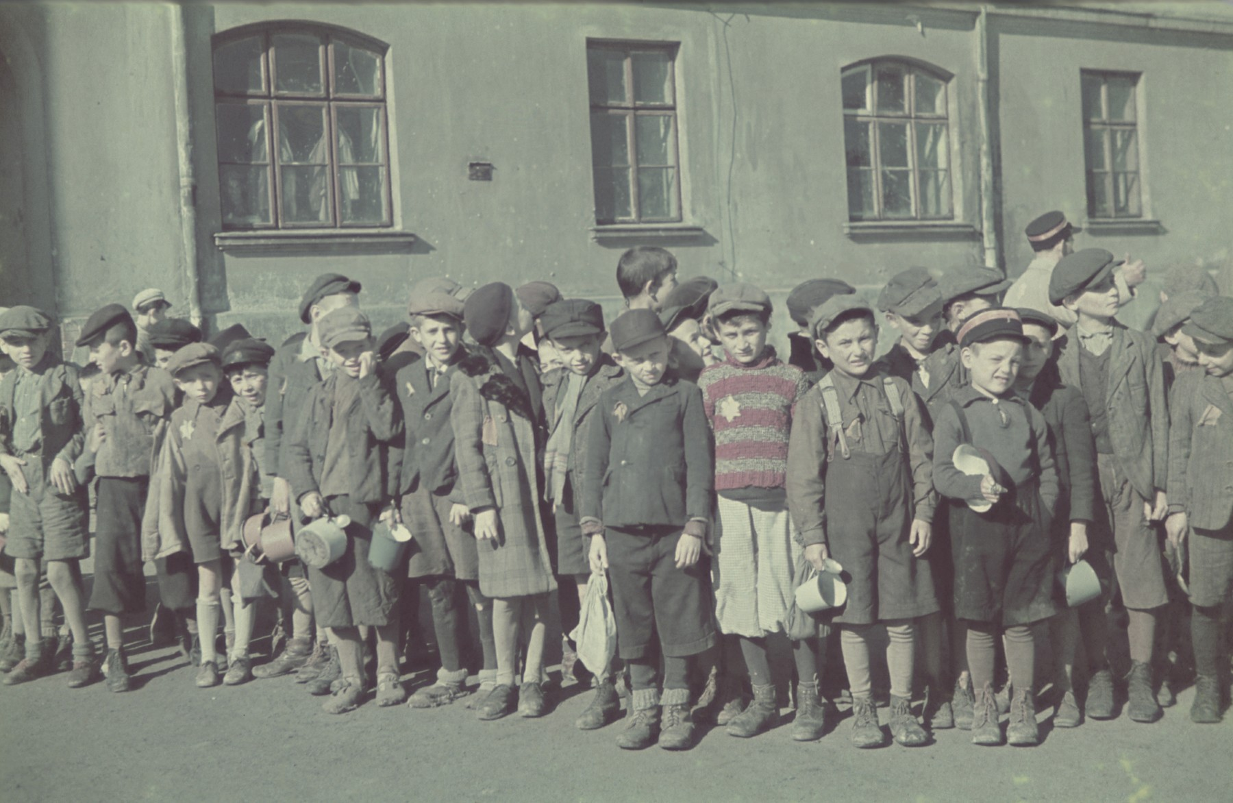 "Ghetto school children holding small pails and cups wait in line outside the ghetto soup kitchen.  Original German caption: ""Schuljugend"" (school children), #146.  Among those pictured is Aleksander Henryk Laks (b. Chaim Cale in 1928), standing below the central pane of the left window, and Sam Pakin (b. Szlamek Pakin), to his left, holding two pails.  Leon Lewkowicz is the seventh from the right with the checkered coat and beret."