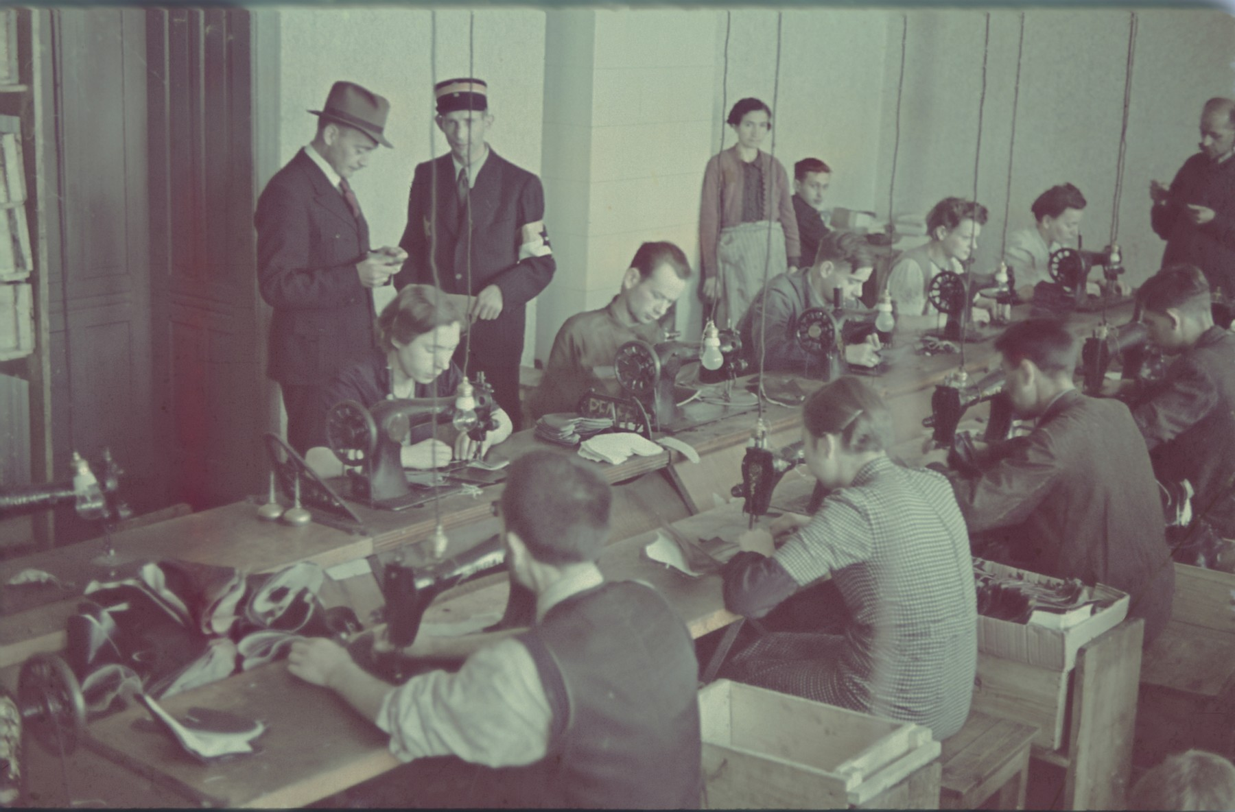"""A Jewish policeman accompanies a supervisor inspecting Jews sewing on machines in the saddle-making workshop in the Lodz ghetto.  Original German caption: """"Litzmannstadt-Getto, Sattlerei"""" (saddlery)."""