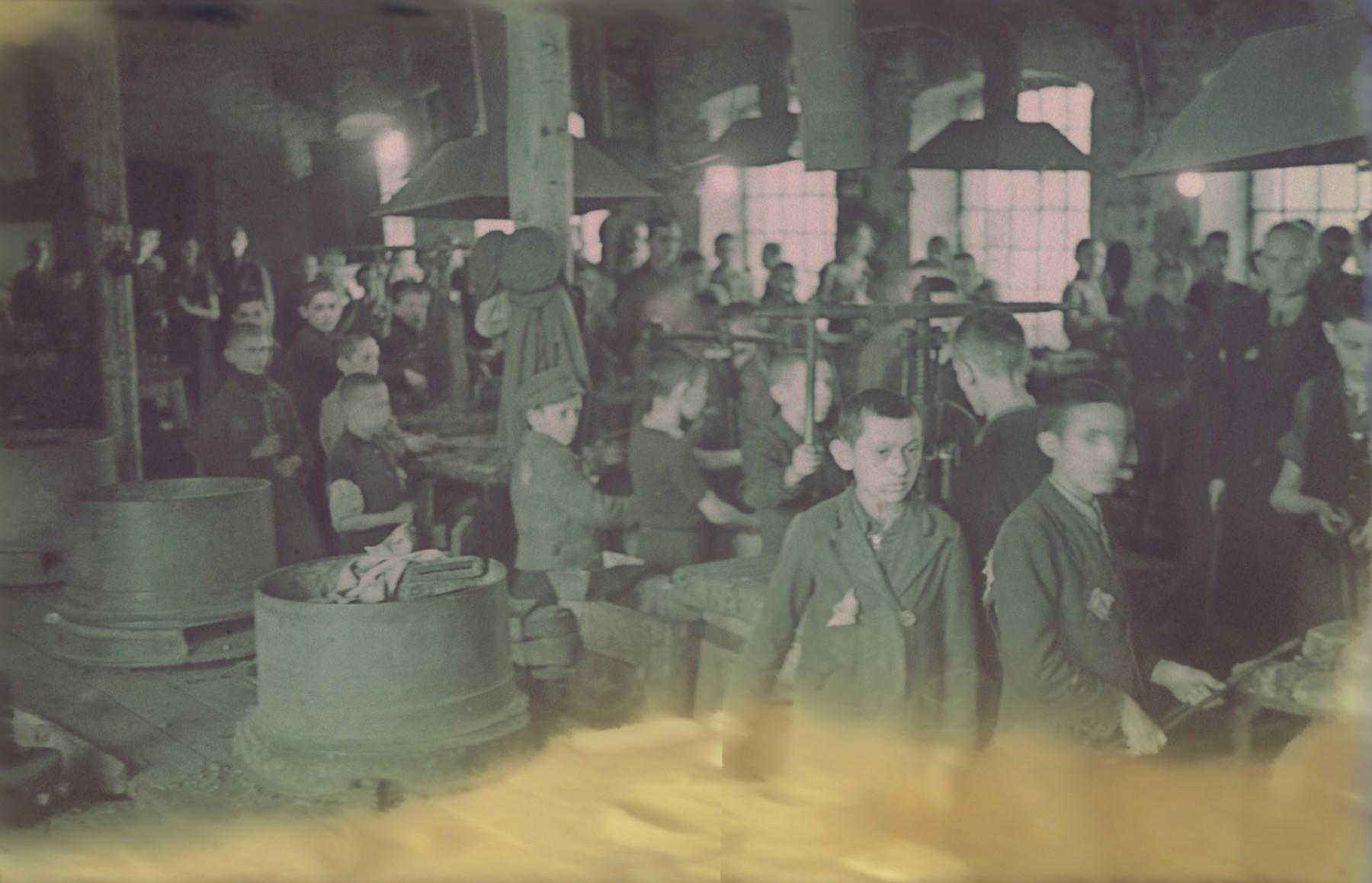 """Jewish children working in a locksmith's workshop in the Lodz ghetto.  Original German caption: """"Getto-Litzmannstadt, """"Schlosserei"""" (locksmith), #15 (number partially blurred)."""