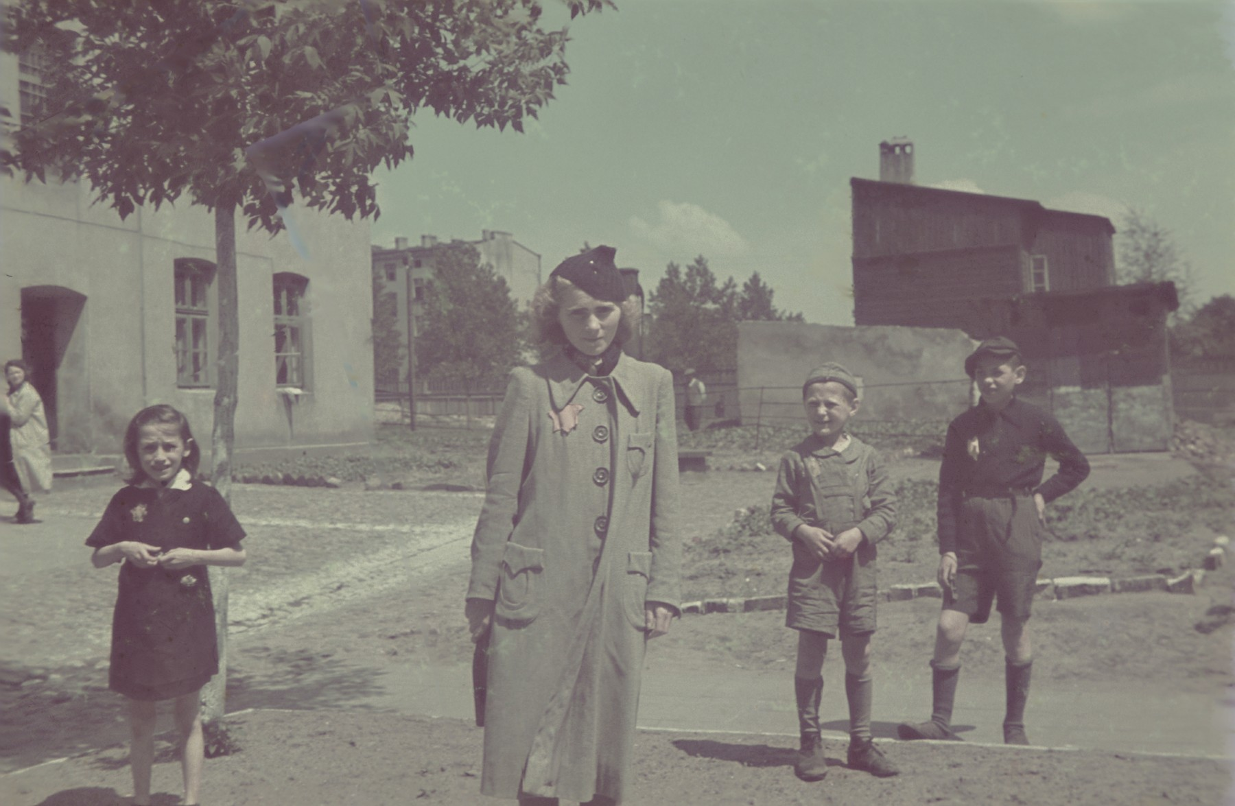 A woman and children all of whom are wearing yellow stars stand on a street corner of the Lodz ghetto.