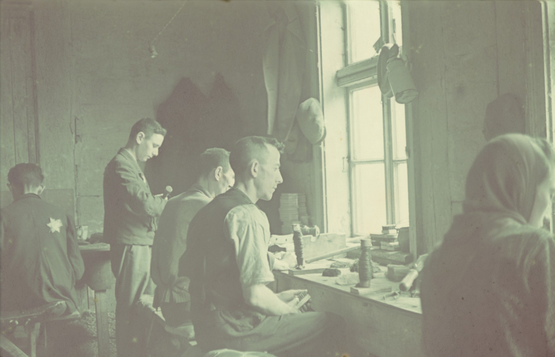 "Workers carve wood in a factory in the Lodz ghetto.  Original German caption: ""Getto, Litzmannstadt, Leisentfabrik"" (wooden trim factory), #133."