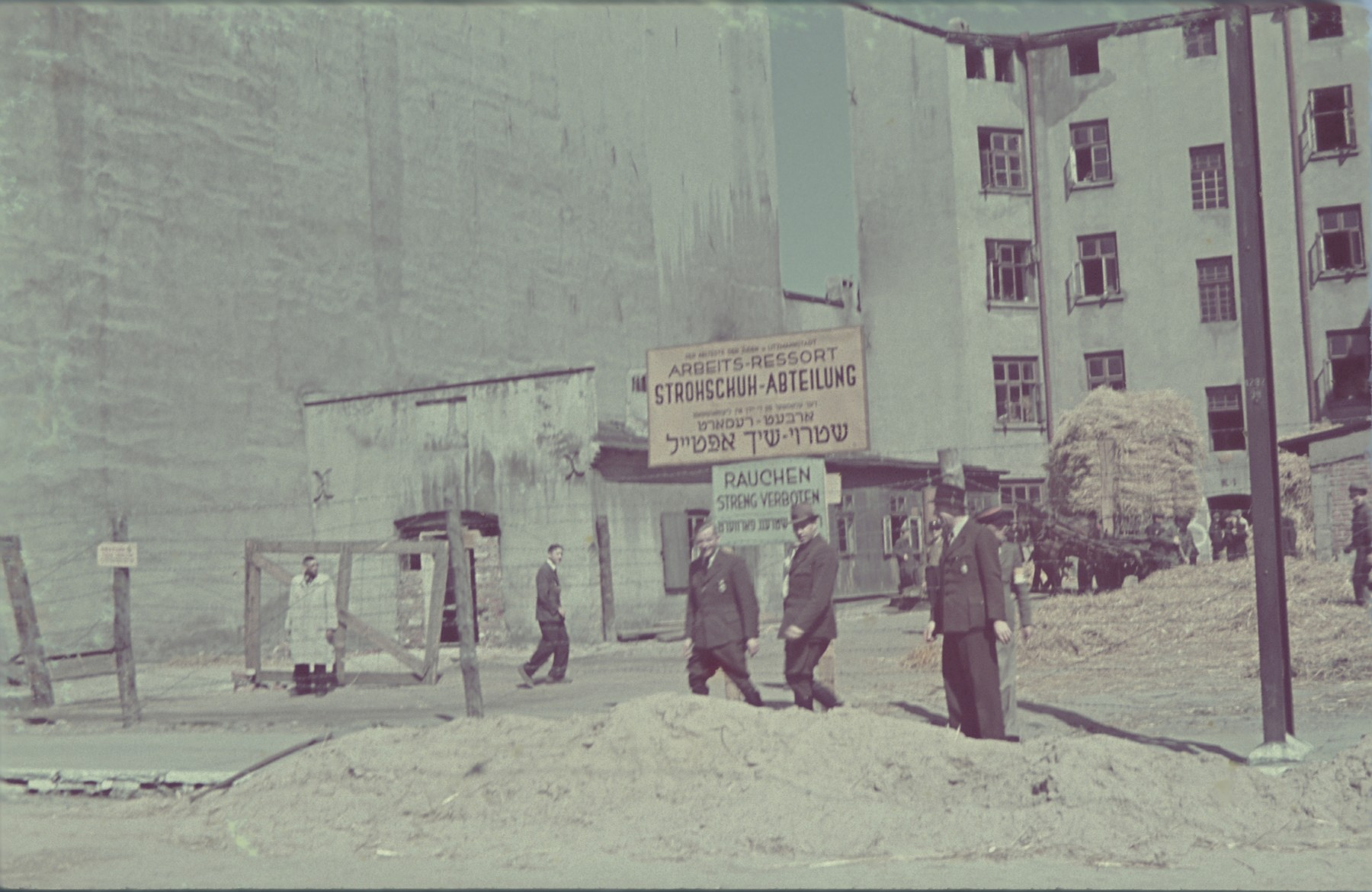 "Three men walk past the entrance to the straw shoe workshop in the Lodz ghetto.  Original German caption: ""Litzmannstadt-Getto, Strohschufabrik"" (straw shoe factory), #200."