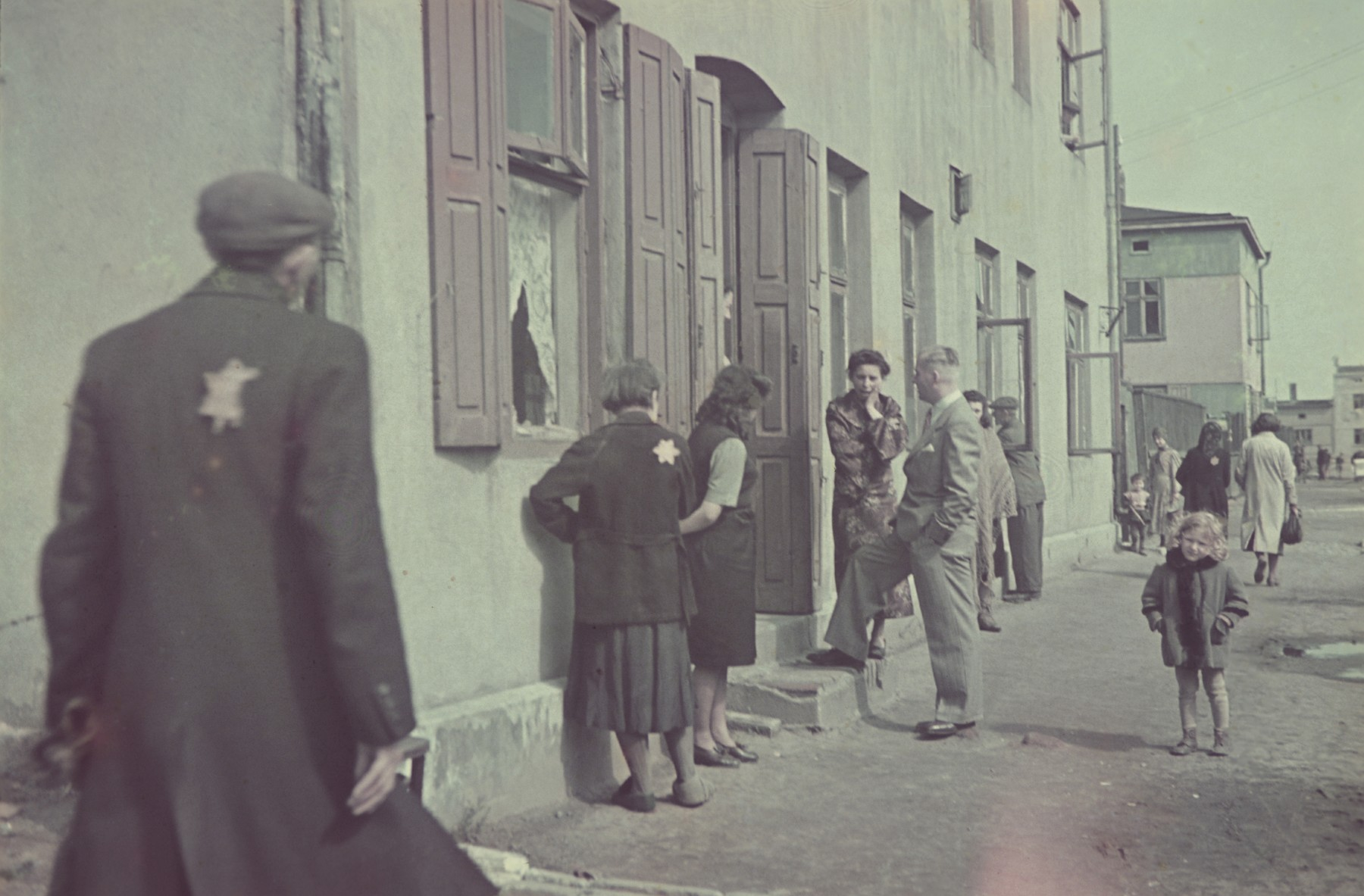Hans Biebow, German administrator of the Lodz ghetto, talks to a goup of Jewish women on the doorstep of a building in the Lodz ghetto.