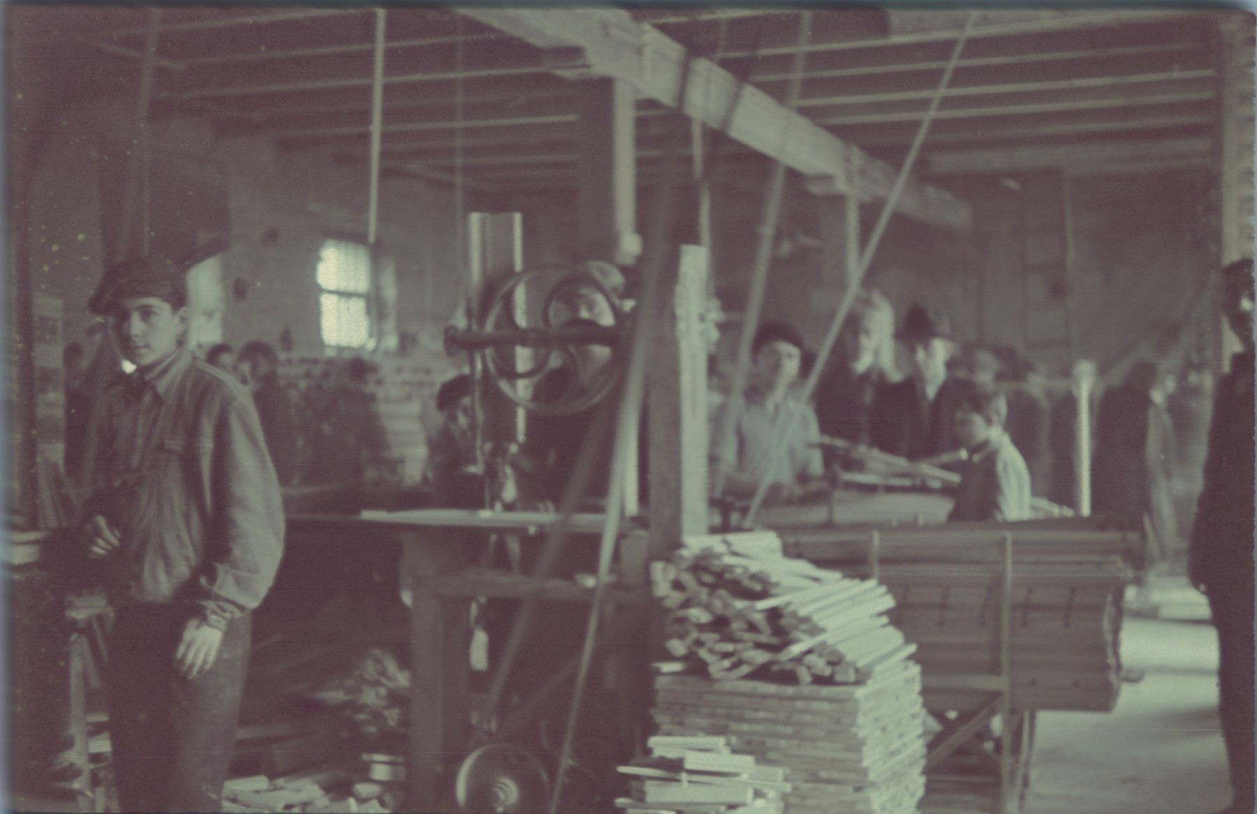 """Wood workers in the furniture factory in the Lodz ghetto.  Original German caption: """"Litzmannstadt Getto, Moebelfabrik"""" (furniture factory), #13 (number blurry and hard to read)."""