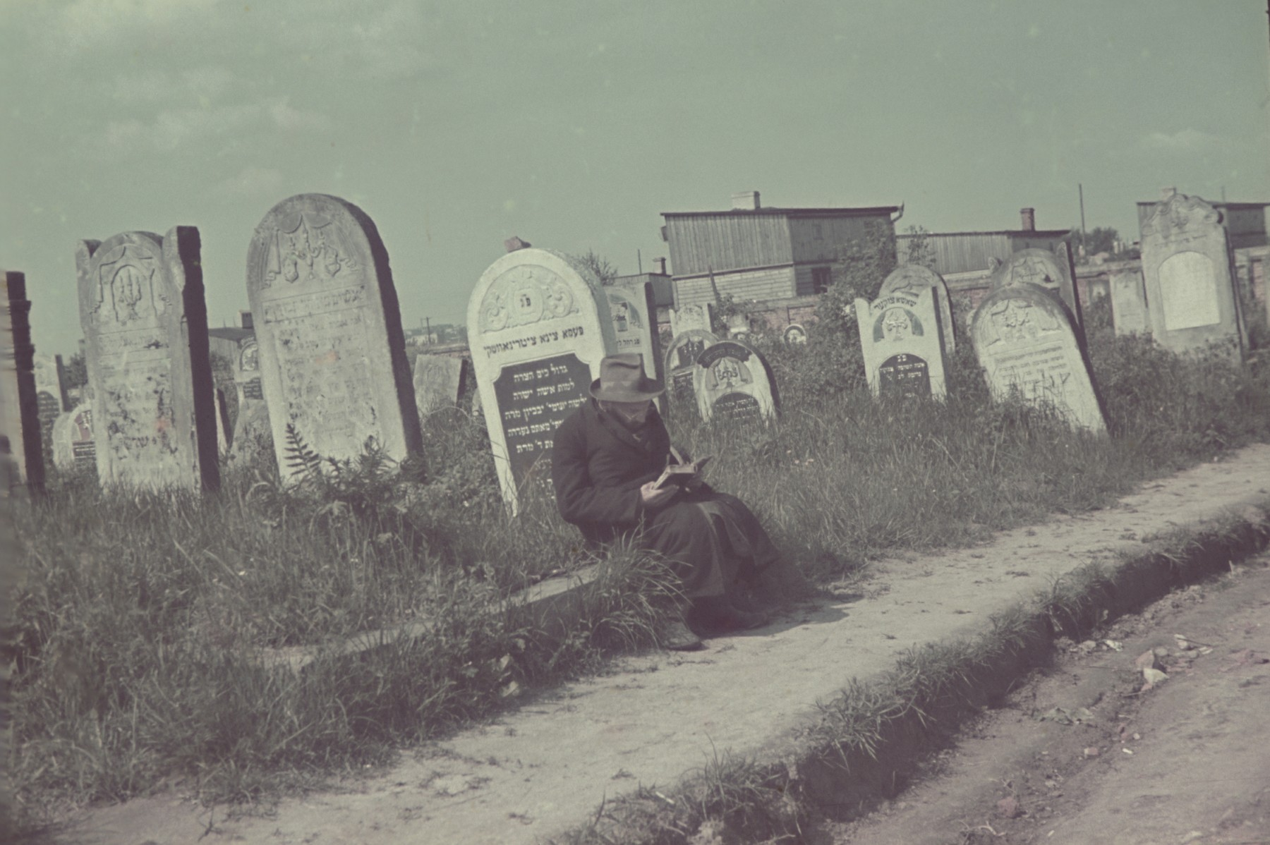 A bearded Jew reads a book next to a tombstone in the Lodz ghetto cemetery.
