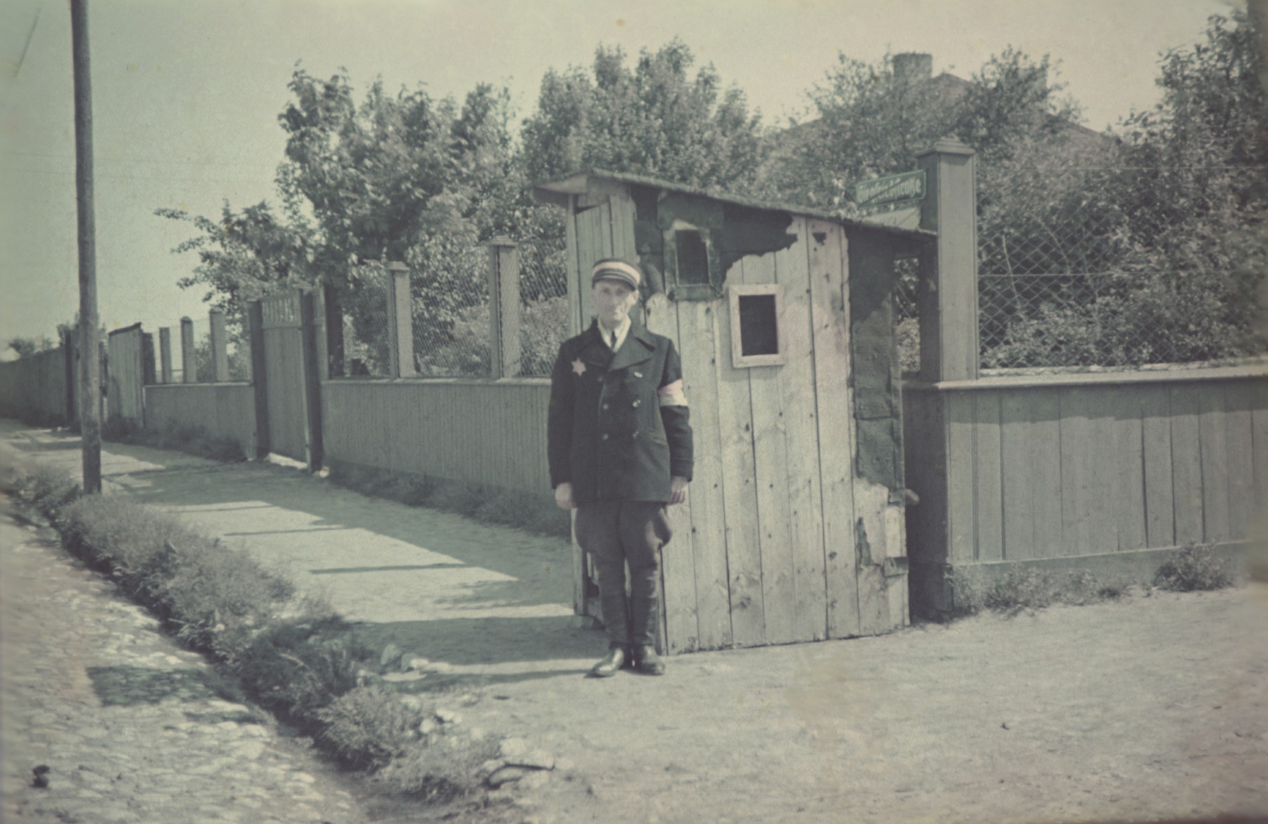 A Jewish border policeman stands by a guardhouse on a street corner in the Lodz ghetto.