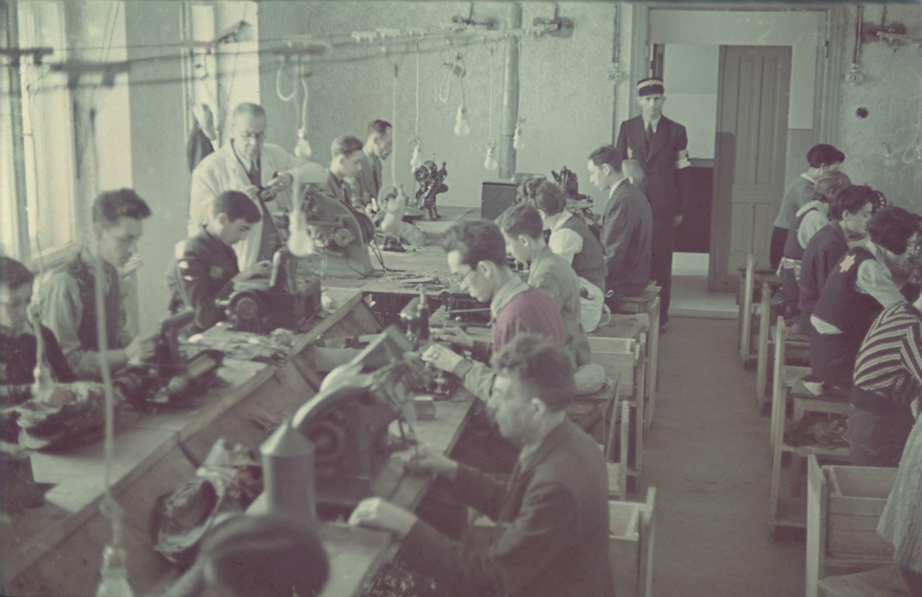 "Workers in the saddle-making workshop in the Lodz ghetto.  Original German caption: ""Litzmannstadt-Getto, Sattlerei"" (saddlery)."